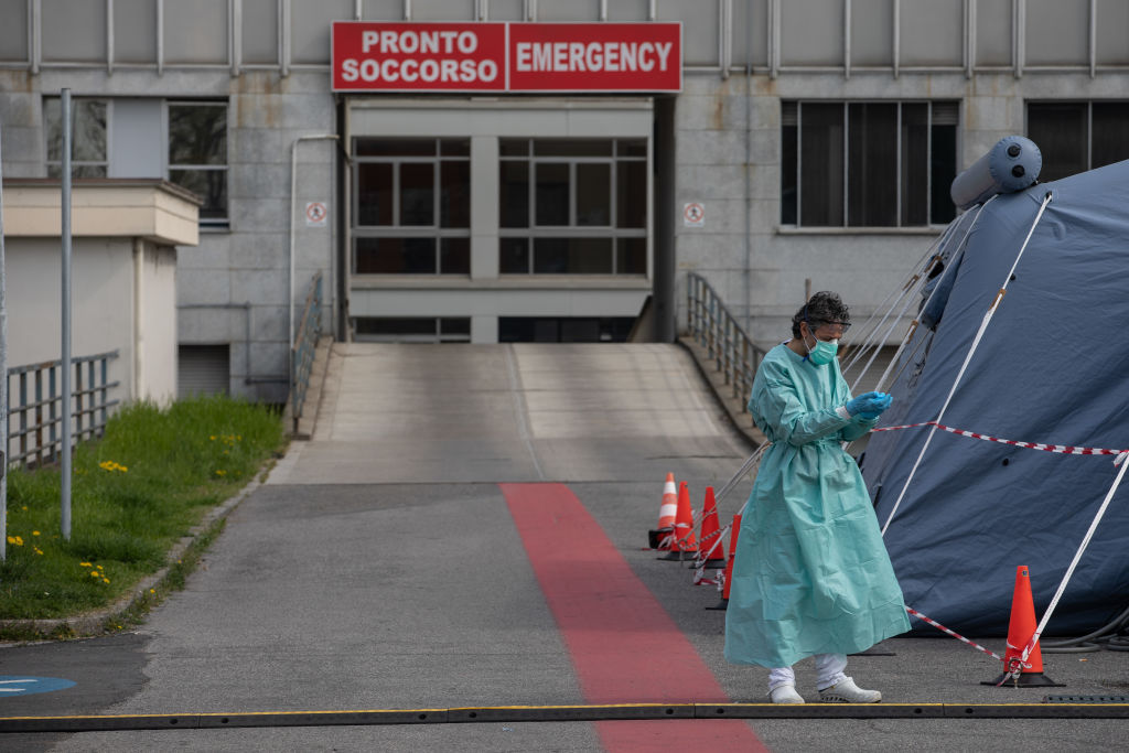 A nurse stands next to a pre-triage tent outside a hospital in Cremona, near Milan.
