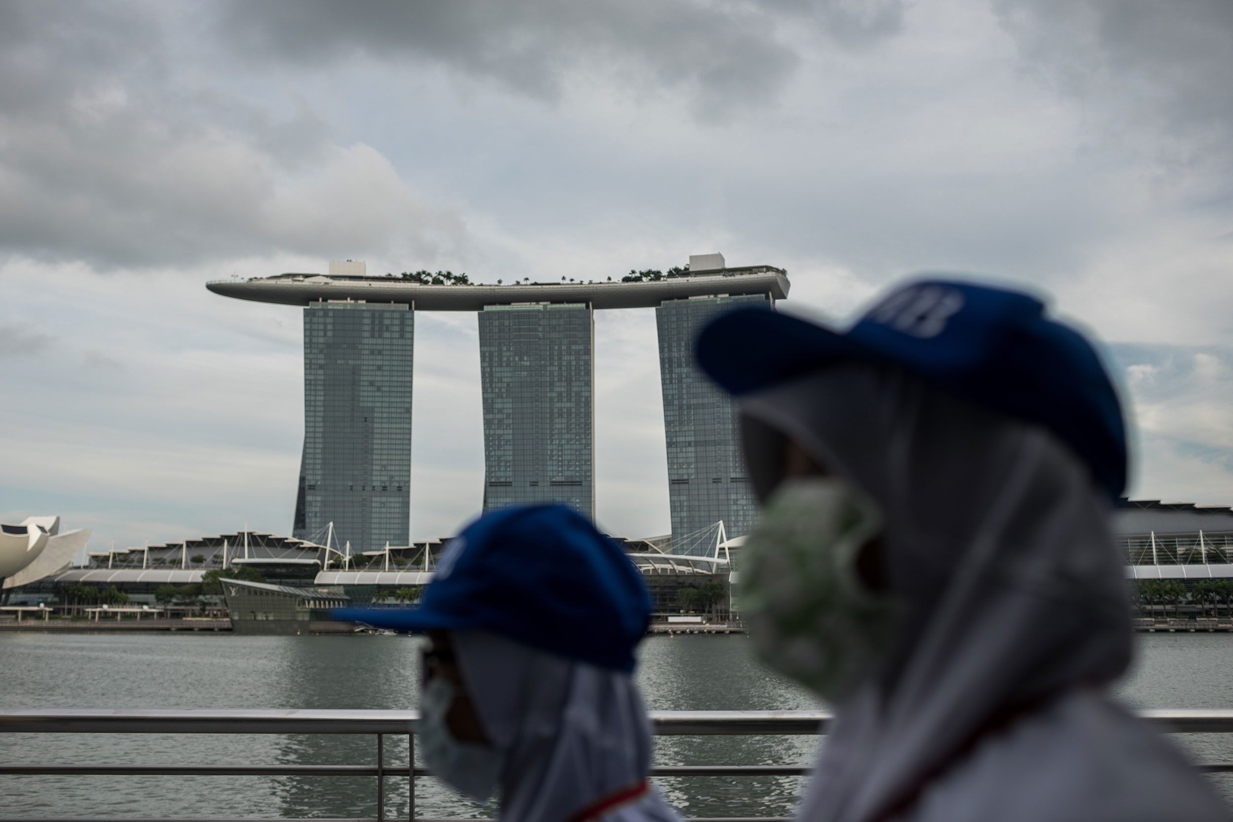 People wearing protective masks walk towards Merlion Park in Singapore on February 12.