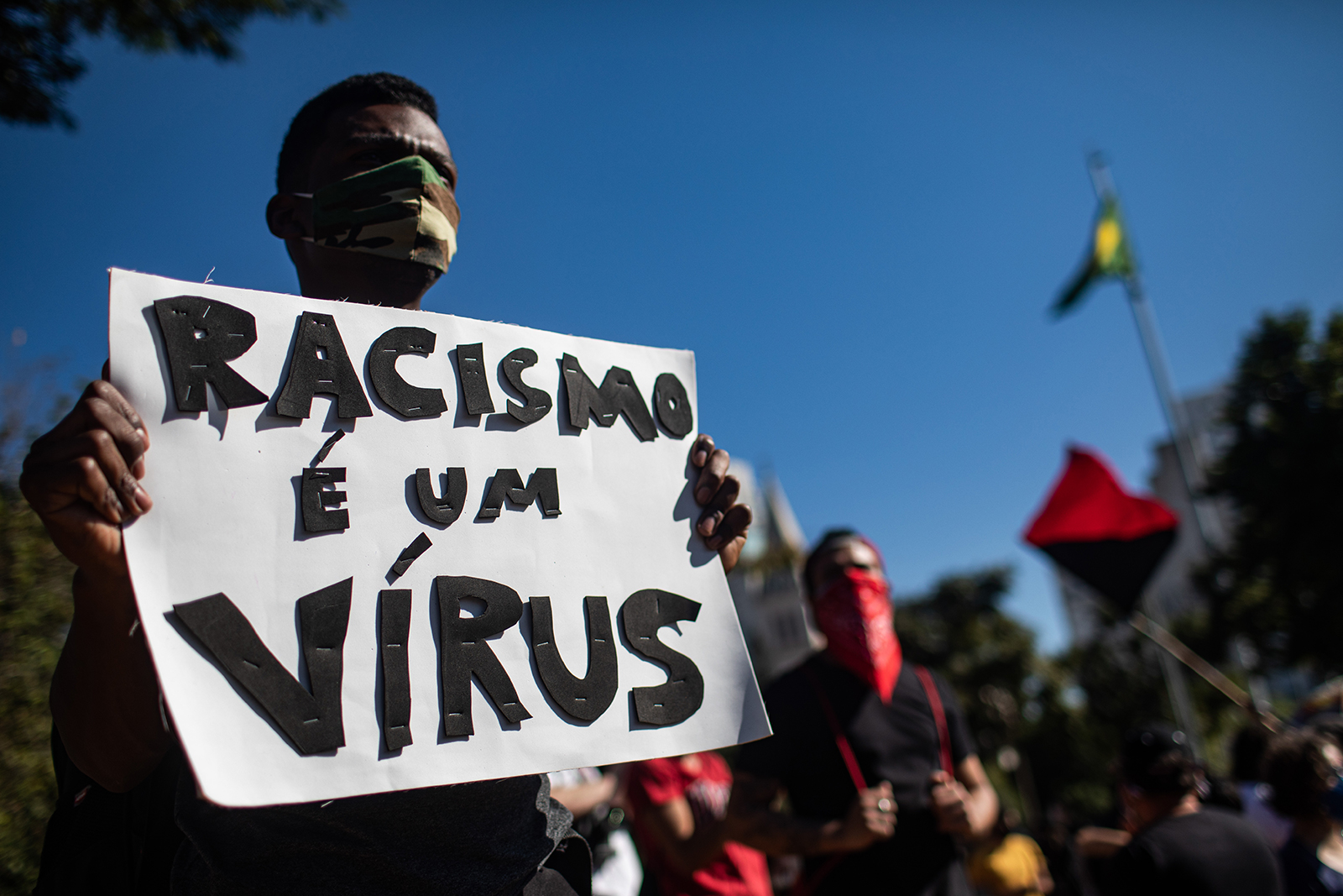 "A demonstrator holds a sign reading, ""Racism is a virus"", during a Black Lives Matter protest on June 7, in Sao Paulo, Brazil."