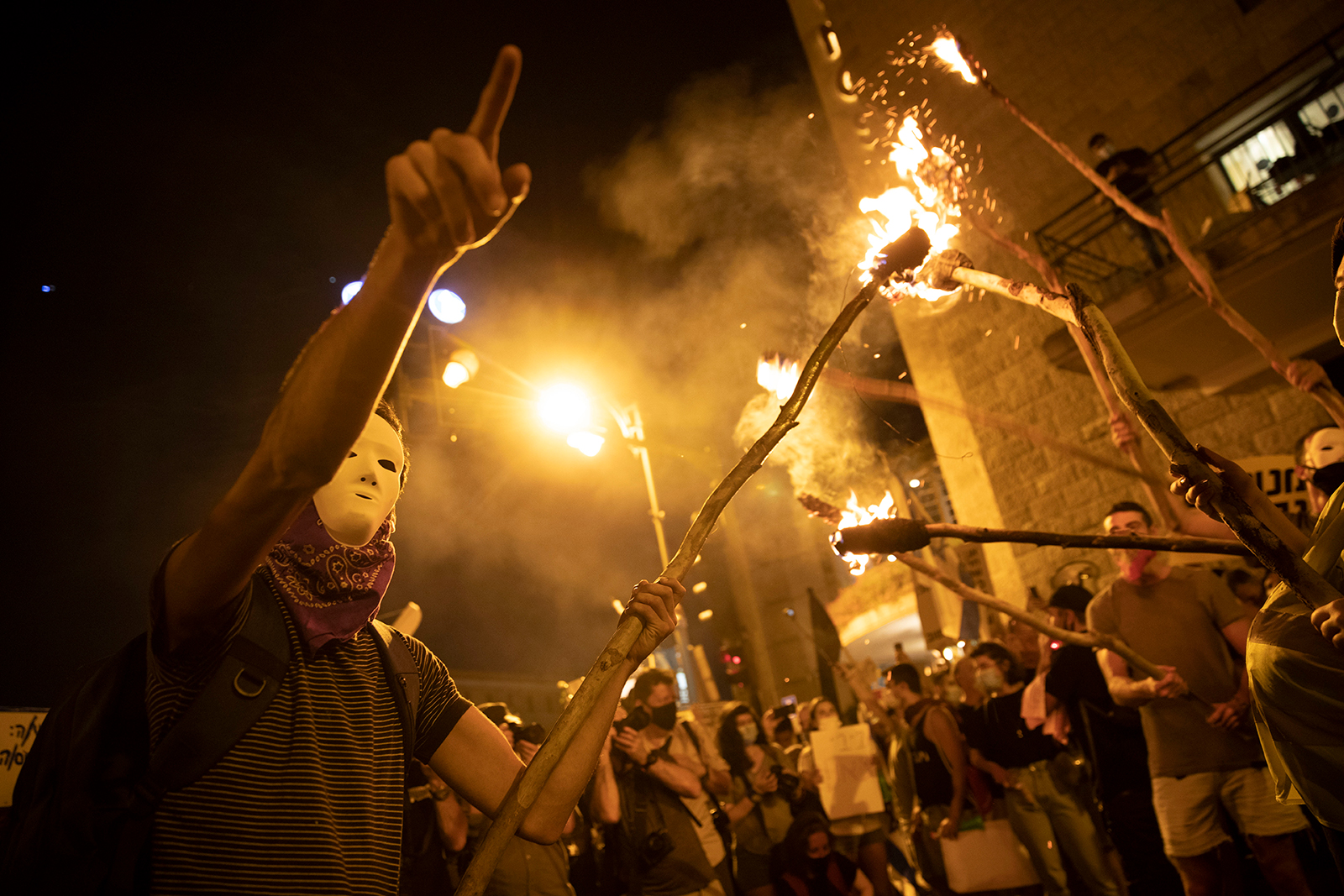 Protesters light torches during a protest against Israel's Prime Minister Benjamin Netanyahu outside his residence in Jerusalem, on August 1.