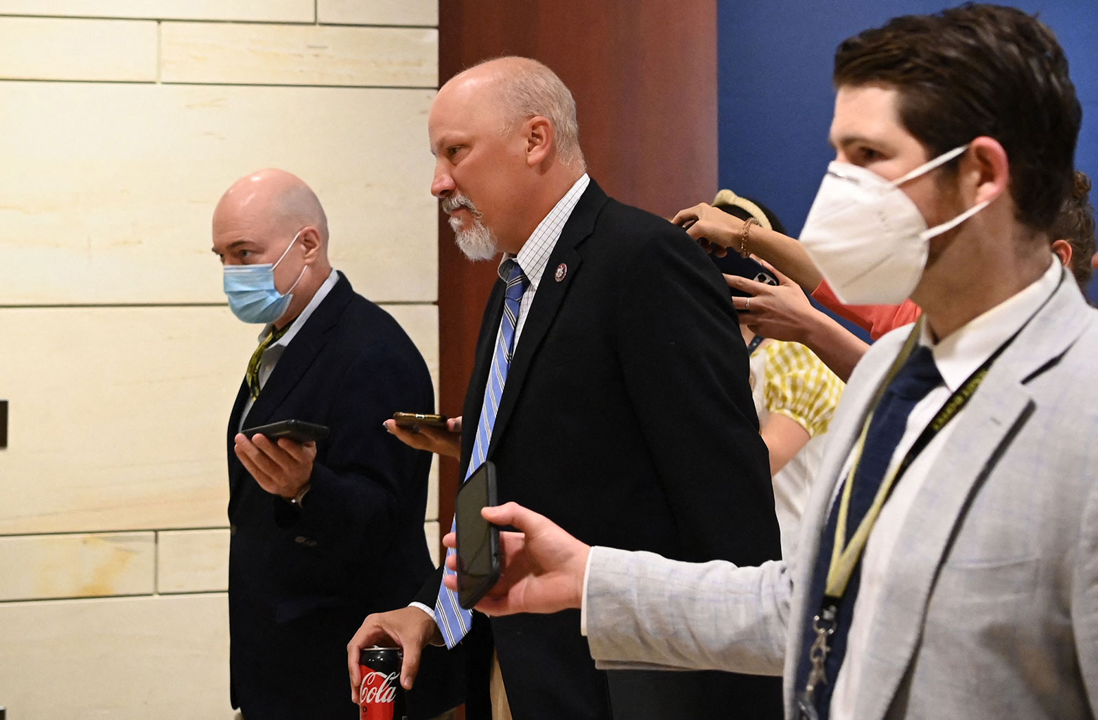 Rep. Chip Roy, center, walks with reporters on Friday.