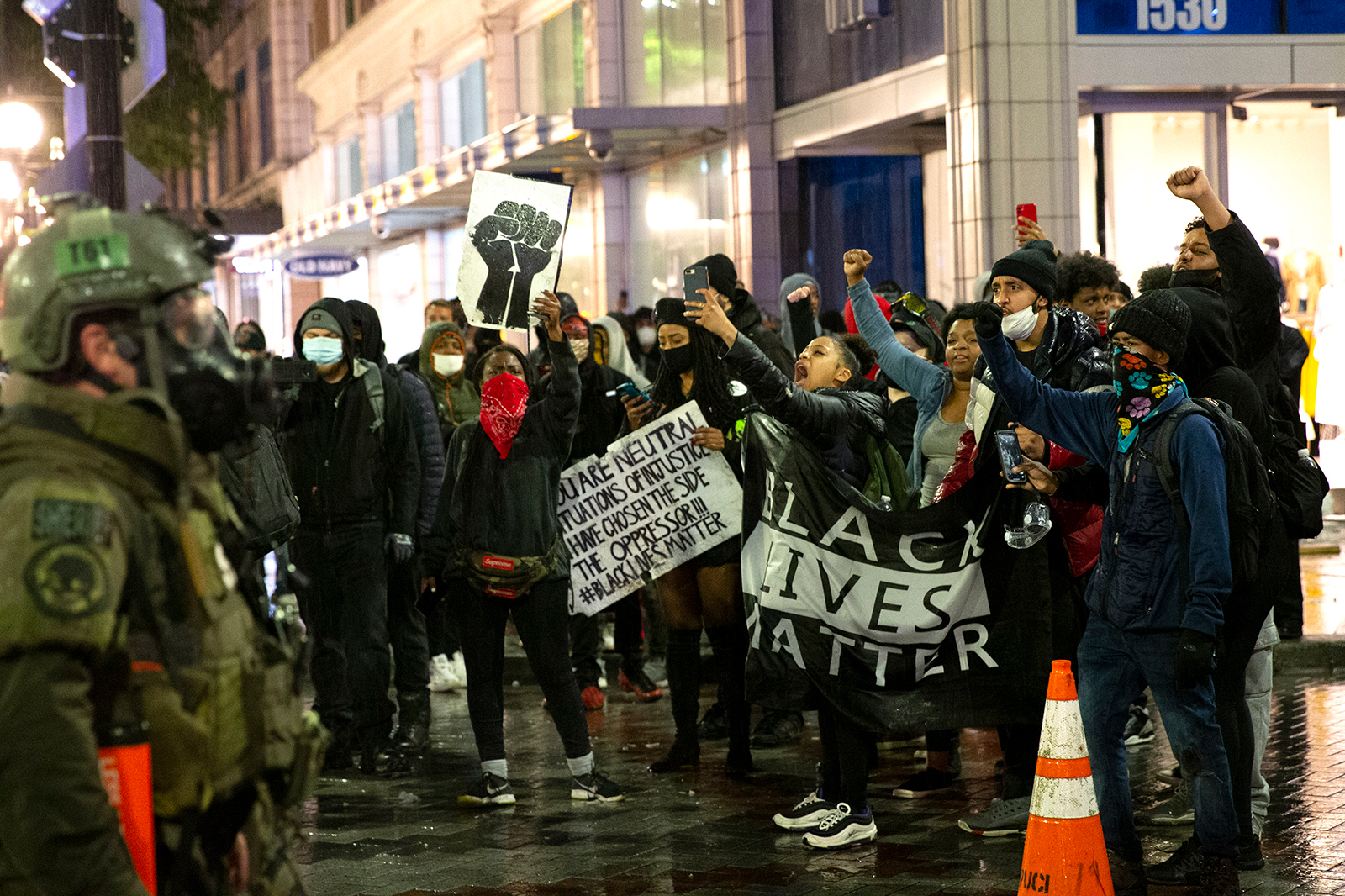Protesters holding a Black Lives Matter banner shout at law enforcement officers on May 30, in Seattle, Washington.