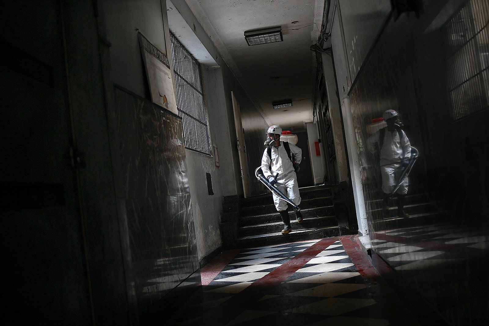 A city worker sprays disinfectant in a building in the Chacao neighborhood of Caracas, Venezuela, Saturday, July 18.
