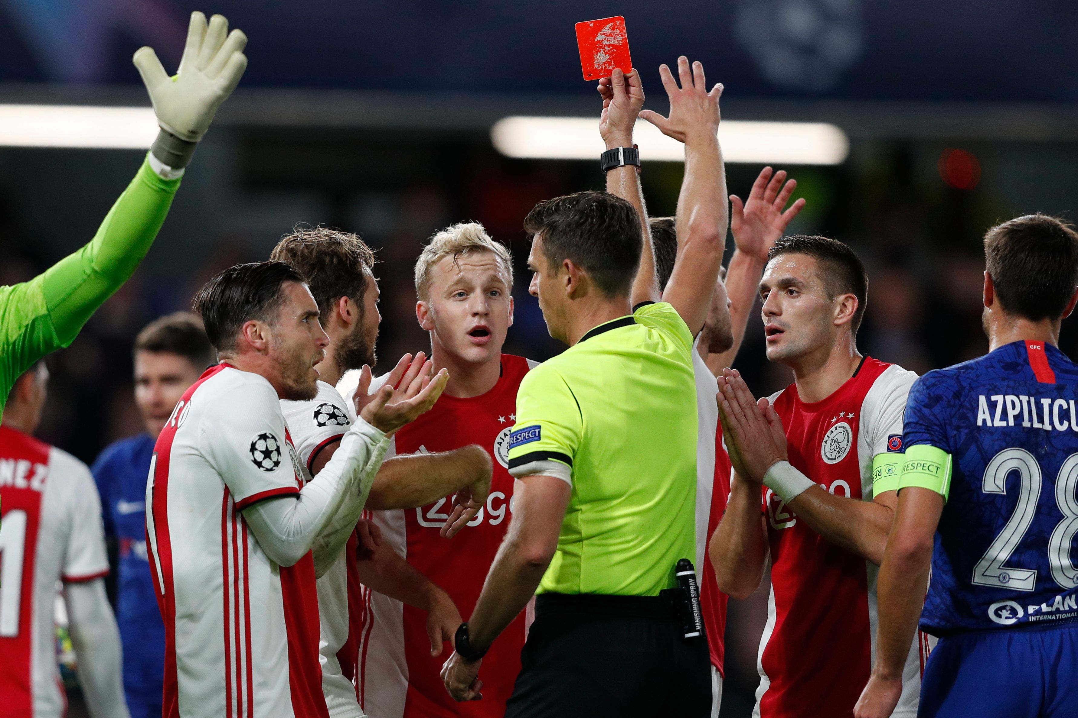 Ajax's players react after its defender Joel Veltman (C) is shown a red card by Italian referee Gianluca Rocchi.