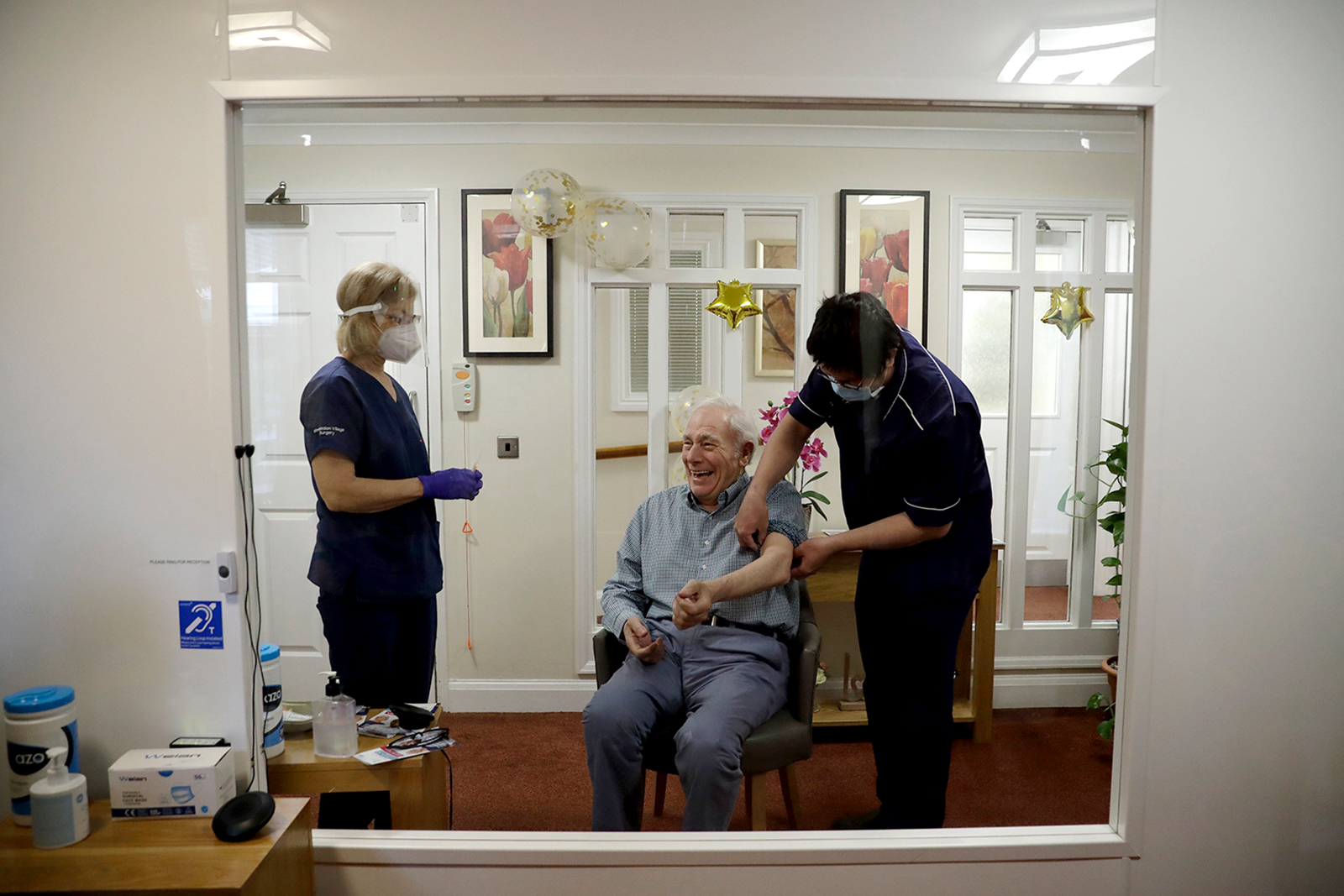 Care home resident Ian Hurley, aged 80, is seen smiling through a viewing screen as his sleeved is rolled up to receive his first dose of the Oxford/AstraZeneca COVID-19 vaccine at the Wimbledon Beaumont Care Home, in London, on January 13.