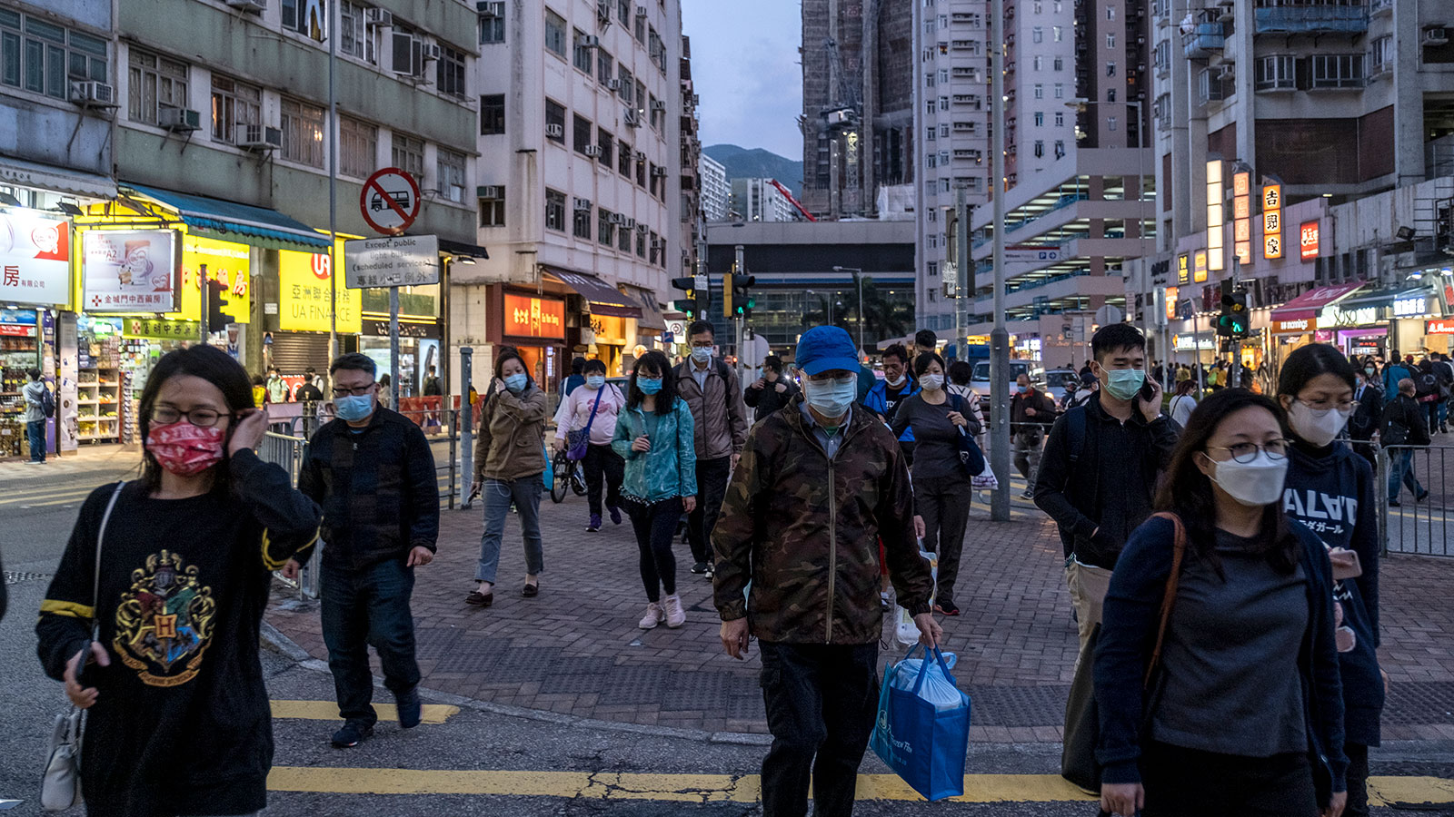 Pedestrians are seen wearing masks as they cross the street in Hong Kong on February 27.