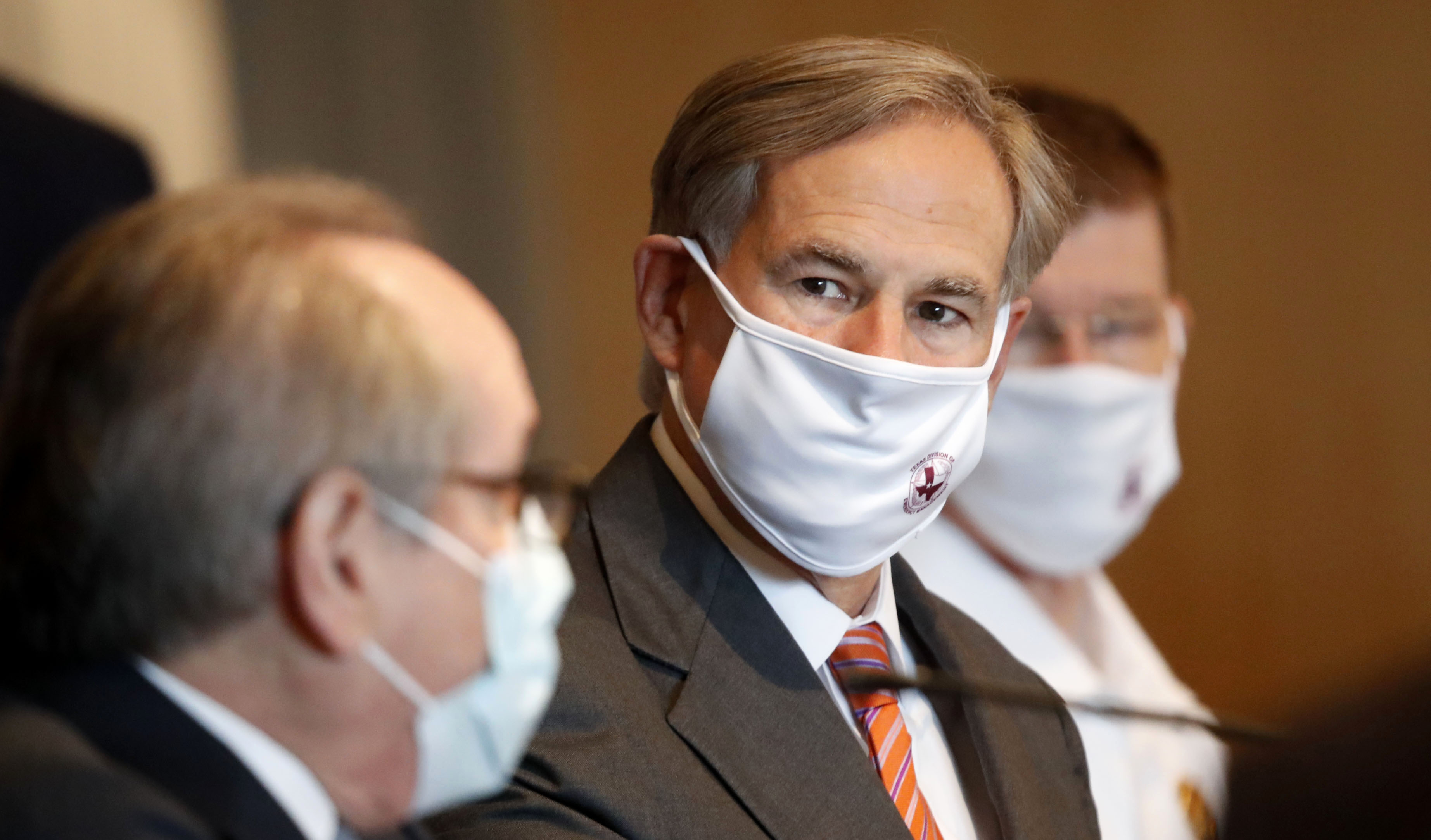 Texas Gov. Greg Abbott, center, listens to Dr. Daniel Podolsky on August 6 during a news conference in Dallas.