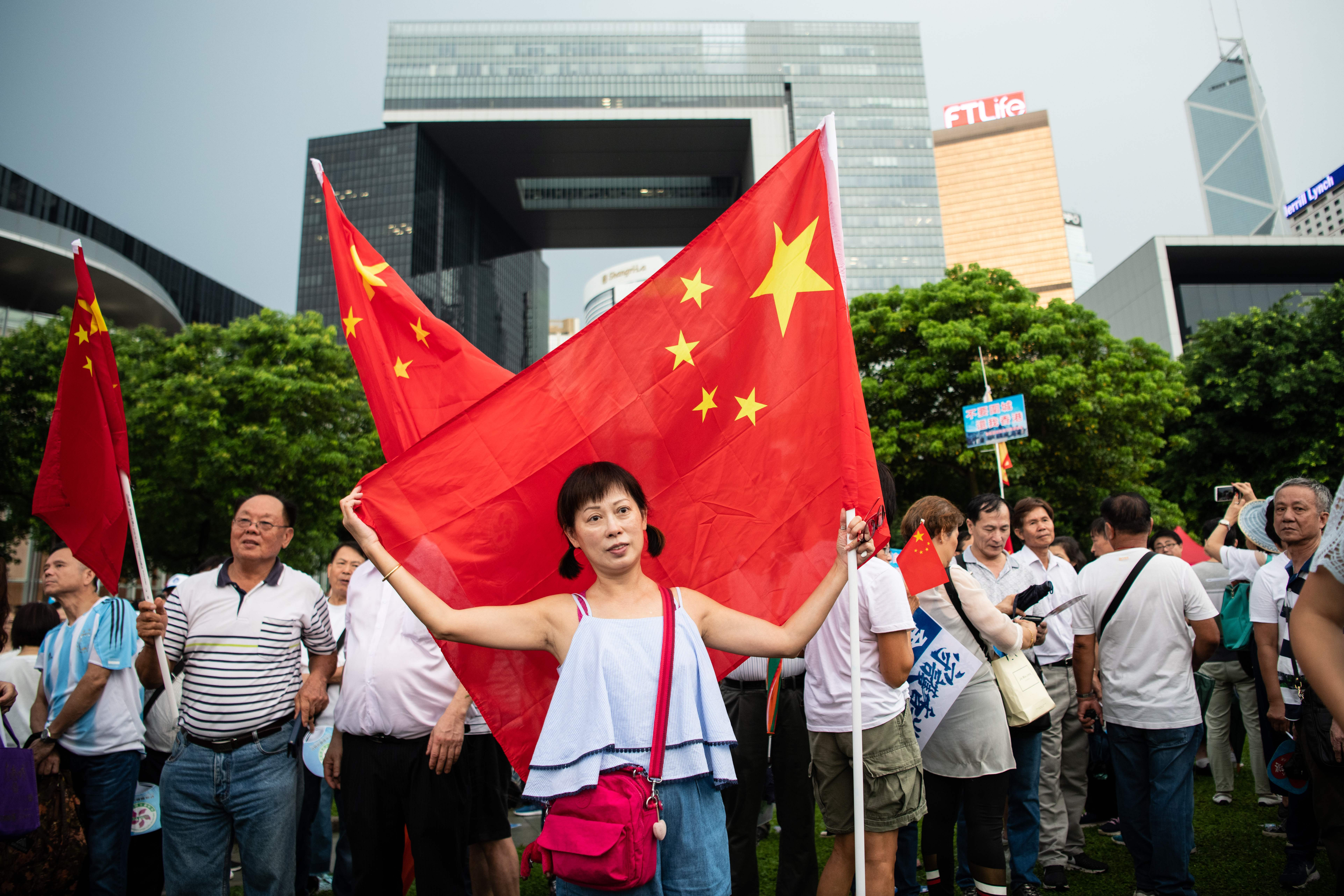 Chinese flags are waved at a rally in support of the police in Hong Kong on July 20, 2019.