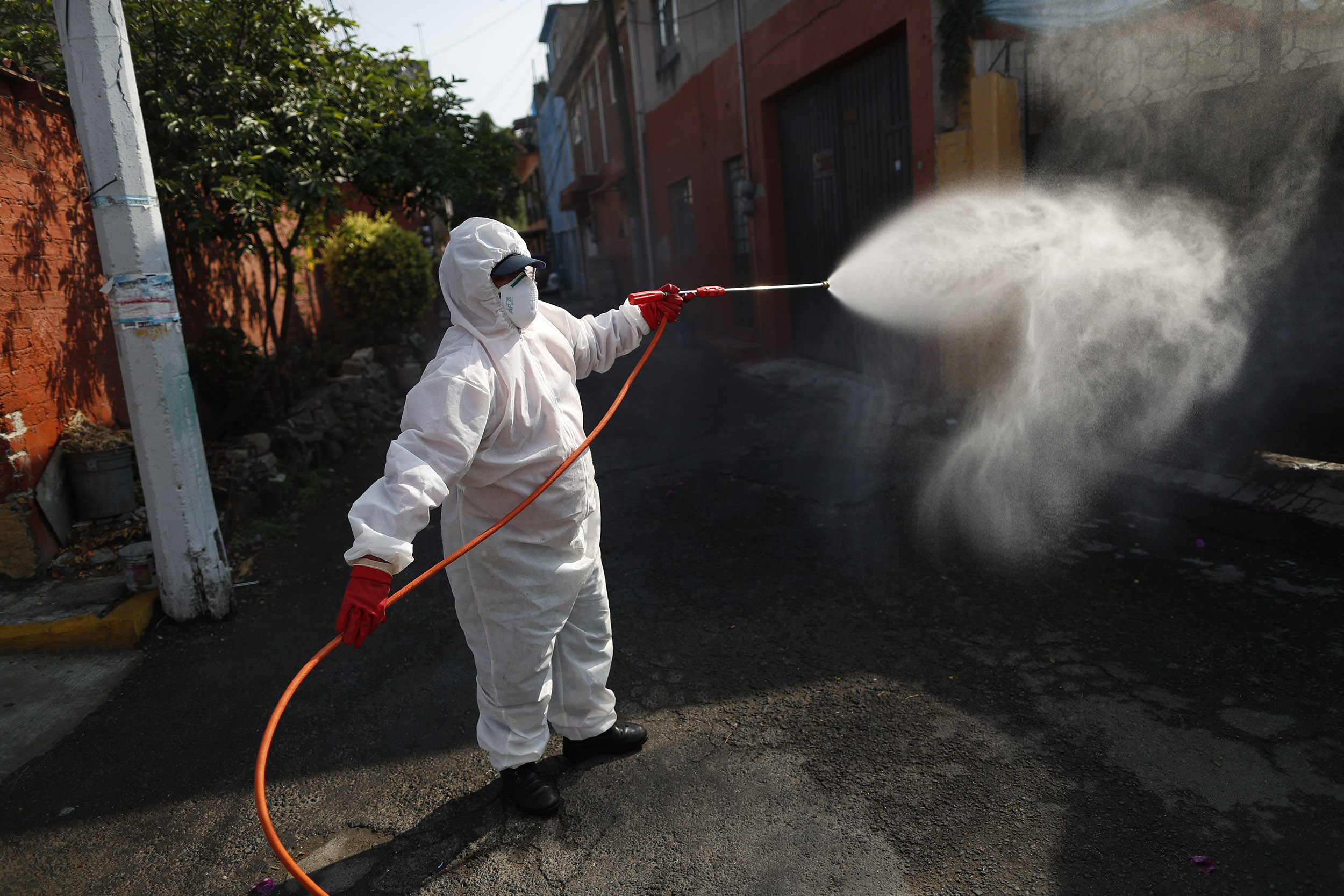 A public safety worker sprays a disinfectant solution in the El Rosario neighborhood of Mexico City, Mexico, on Friday, May 29.