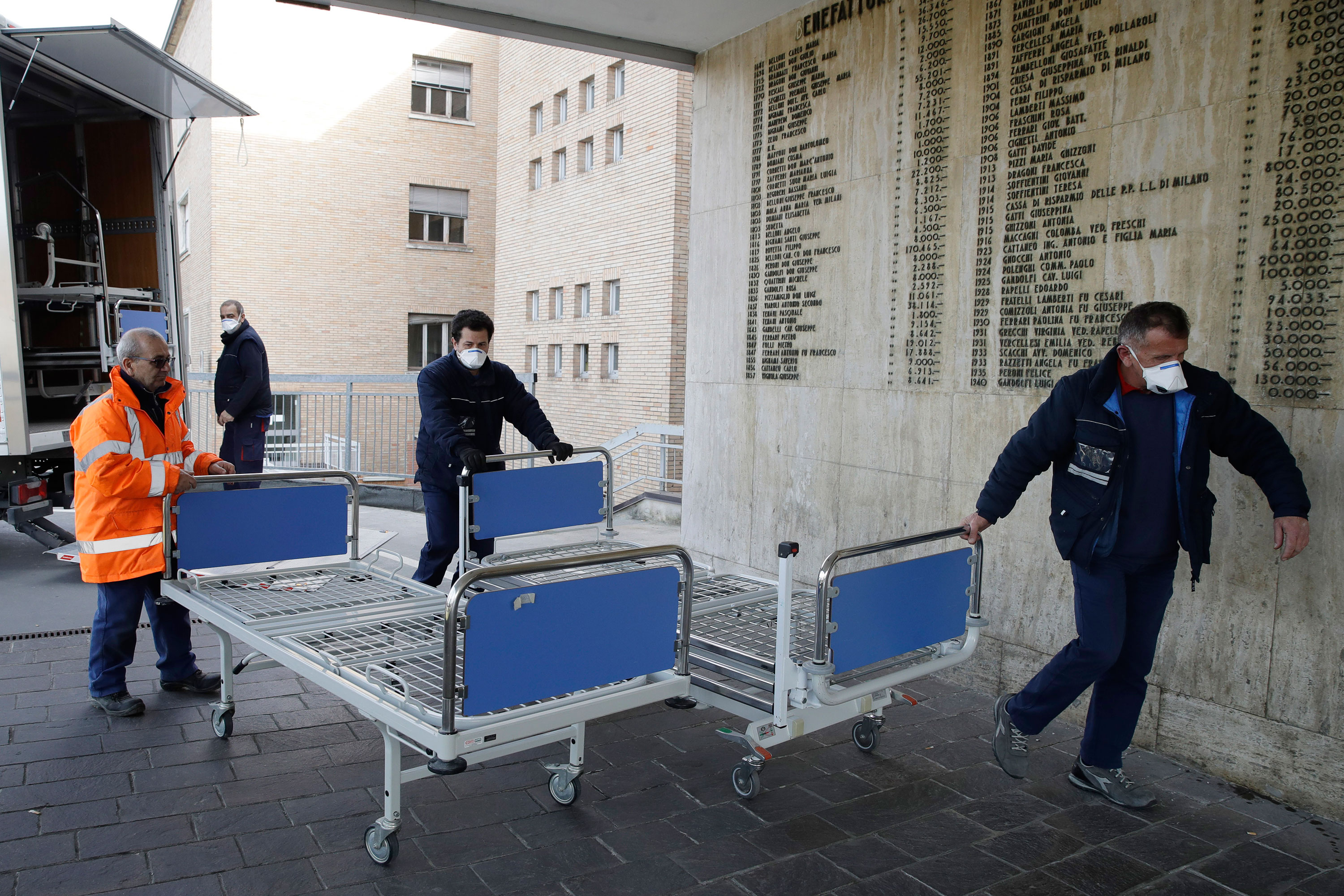 Hospital personnel in Codogno, Italy, carry new beds inside the hospital on Friday, February 21. The hospital is hosting some people who have been diagnosed with the novel coronavirus.