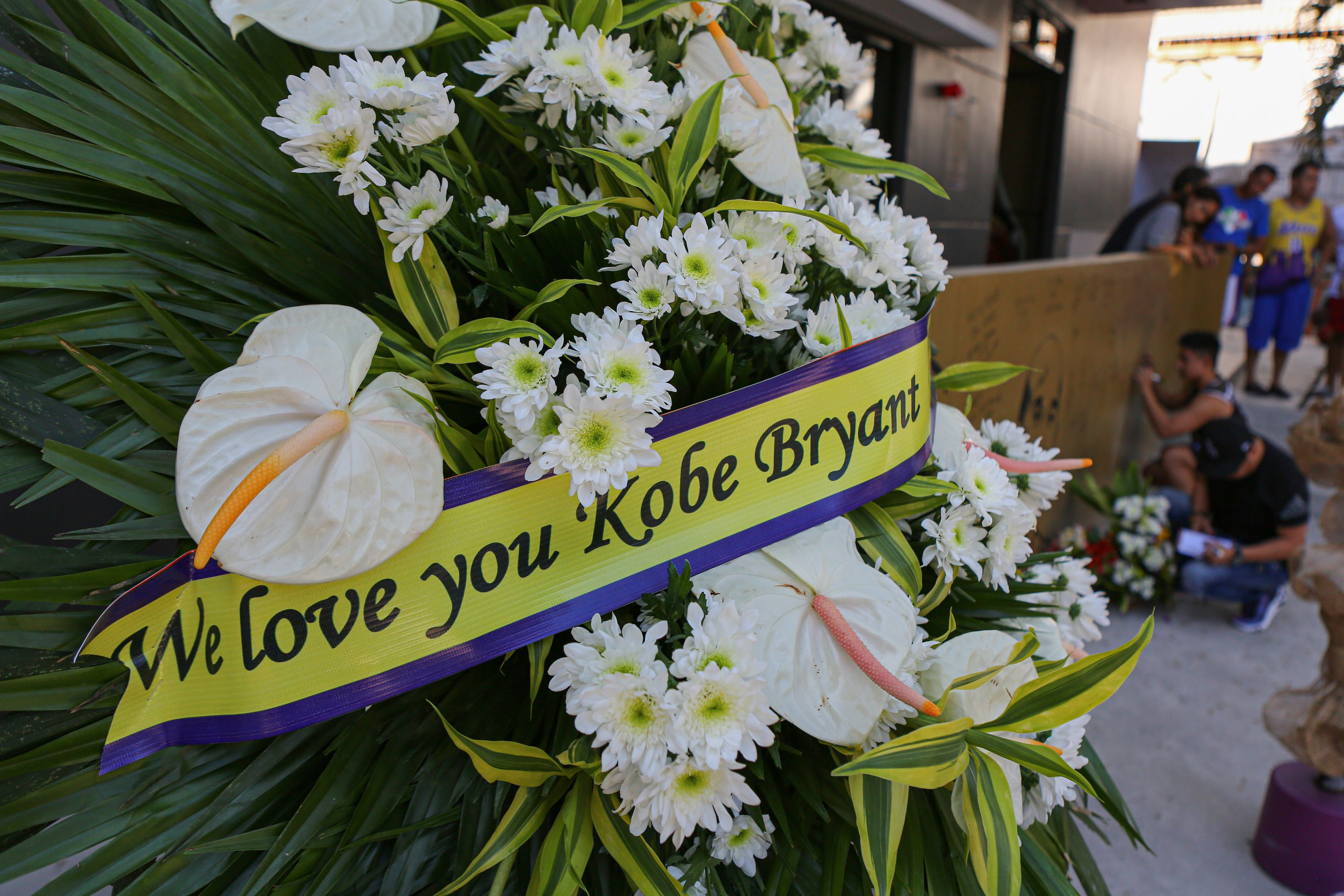 """Fans place flowers and candles at the """"House of Kobe"""" gym."""