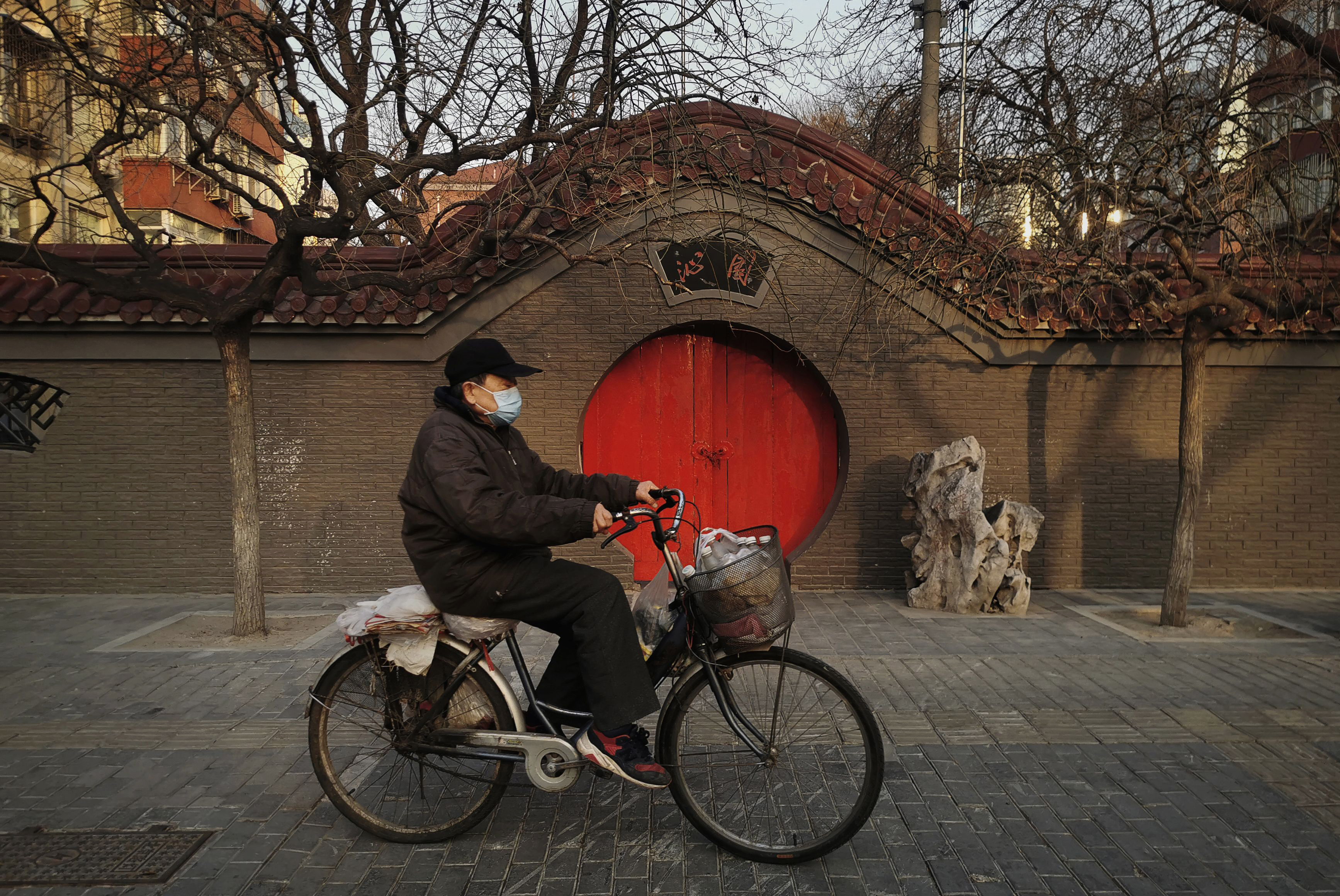 A Chinese man wears a protective mask as he rides his bike on February 23, 2020 in Beijing, China.