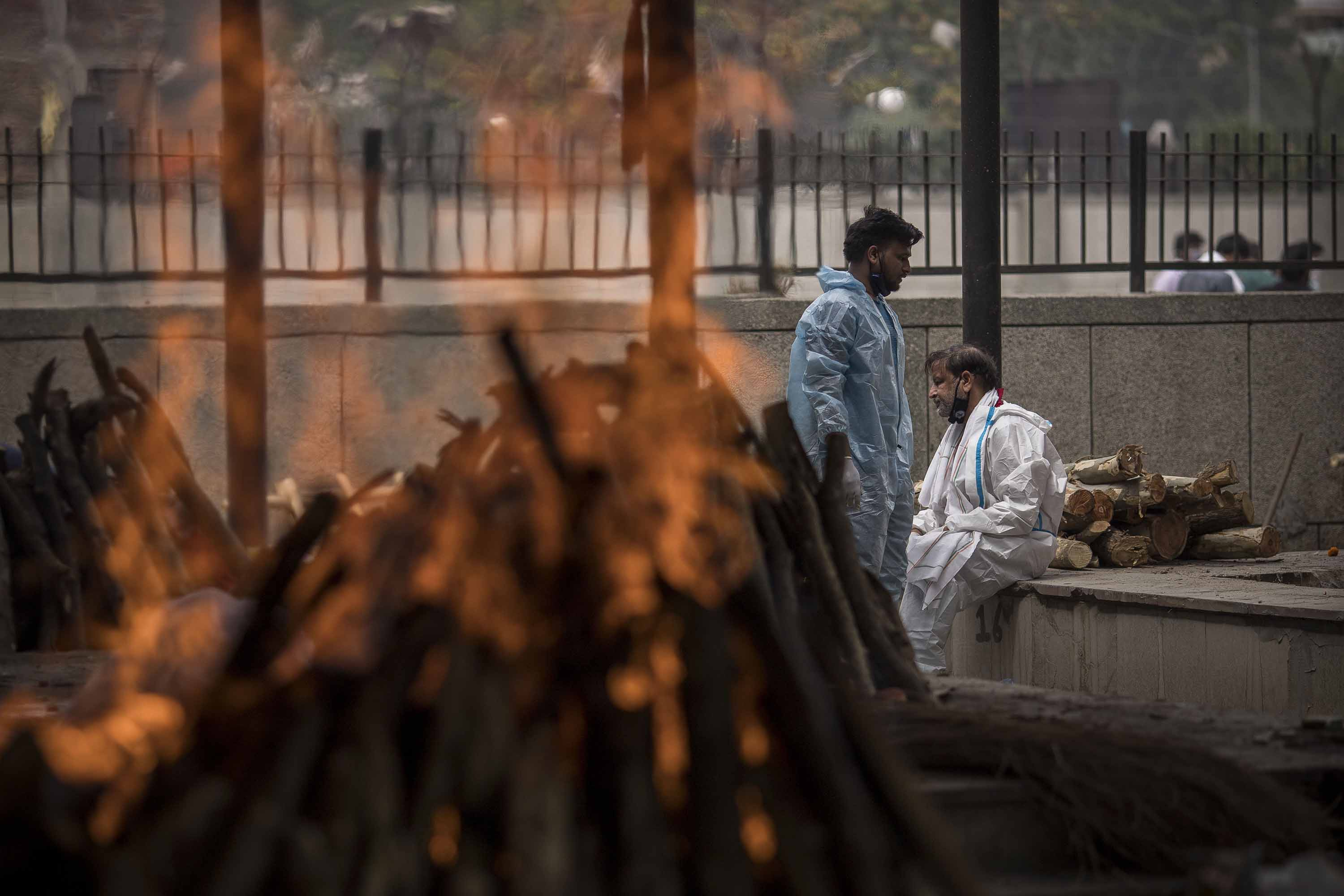 A man performs the last rites for his wife who died of Covid-19 during a mass cremation at a crematorium in New Delhi, India on April 20.