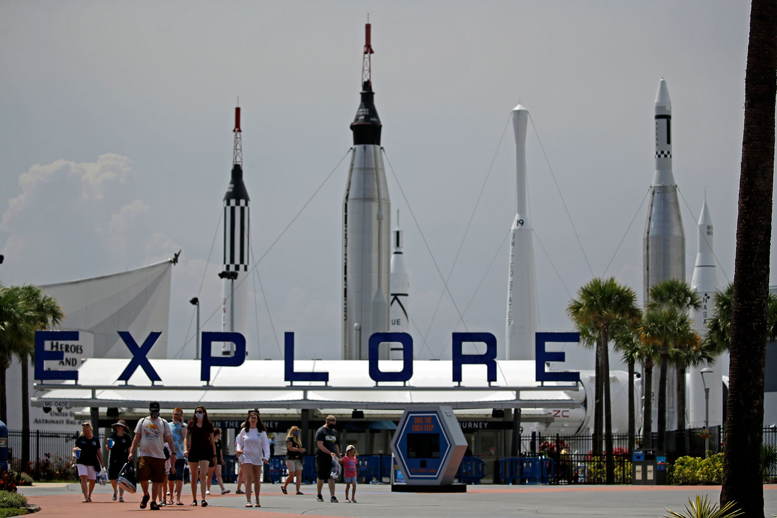 People walk through the Kennedy Space Center Visitor Complex hursday, May 28, 2020, at Cape Canaveral, Fla. The center reopened today after closing March 16 due to the coronavirus pandemic. (AP Photo/Charlie Riedel)