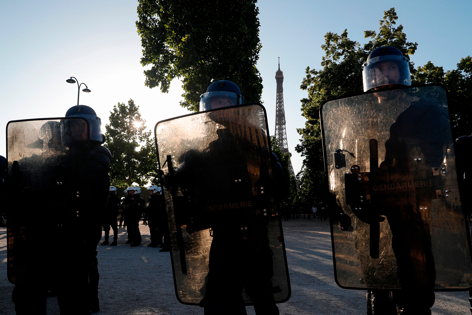 Riot policemen hold their shields with the Eiffel Tower in background during a protest at the Champ de Mars, in Paris on June 6.