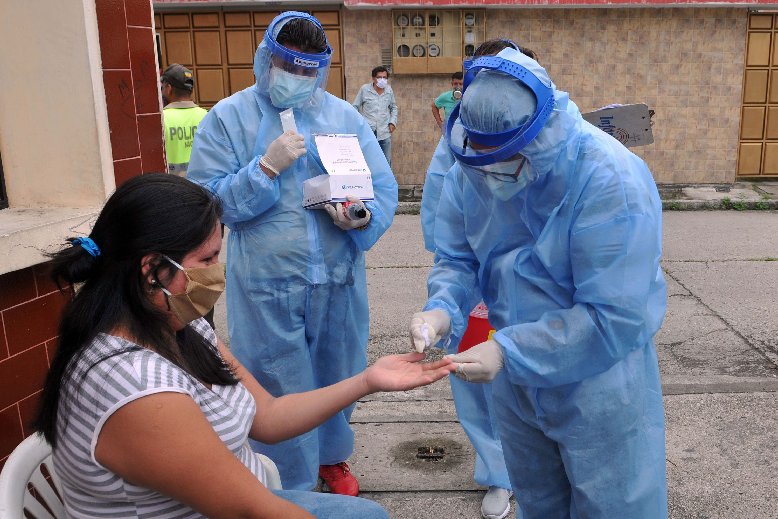 Health workers administer a coronavirus test to a woman in Guayaquil, Ecuador, on April 30.
