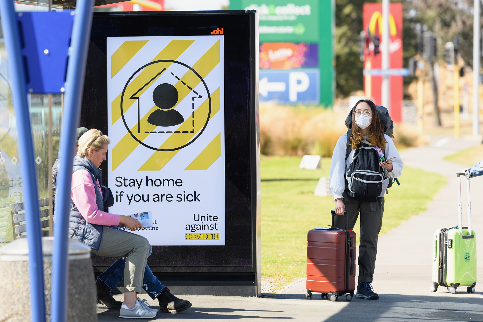 A traveler wearing a protective mask is seen waiting for a bus near Christchurch International Airport on March 18, in Christchurch, New Zealand.
