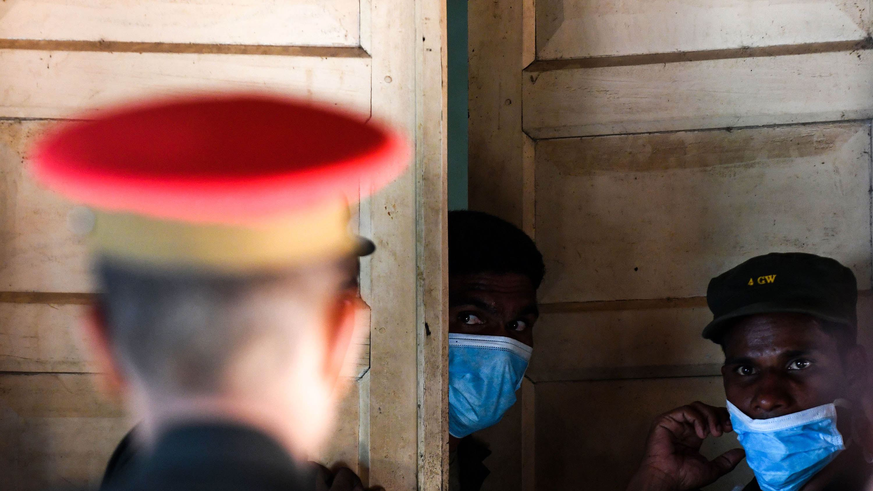 Sri Lankan hospital workers and Army soldiers stand at the door to a morgue following a blast in a church in Batticaloa.