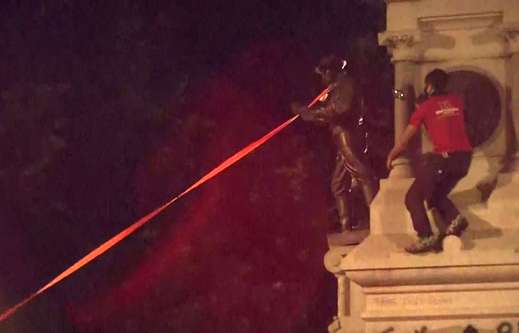 Protesters pull a statue down from a Confederate monument on Friday night in Raleigh, North Carolina.