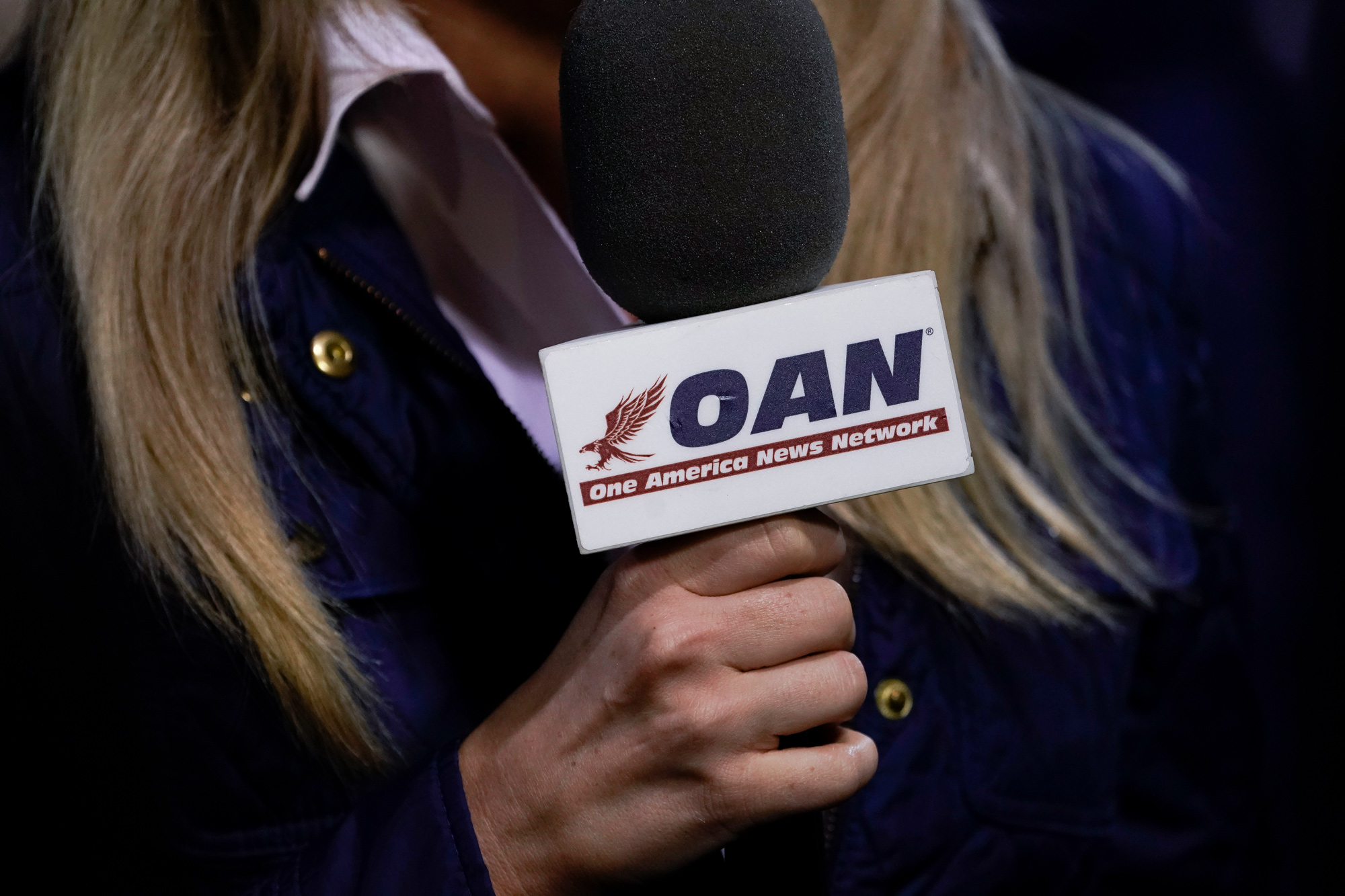 A reporter with One America News Network works at a campaign rally at Newport News/Williamsburg International Airport on September 25 in Newport News, Virginia.