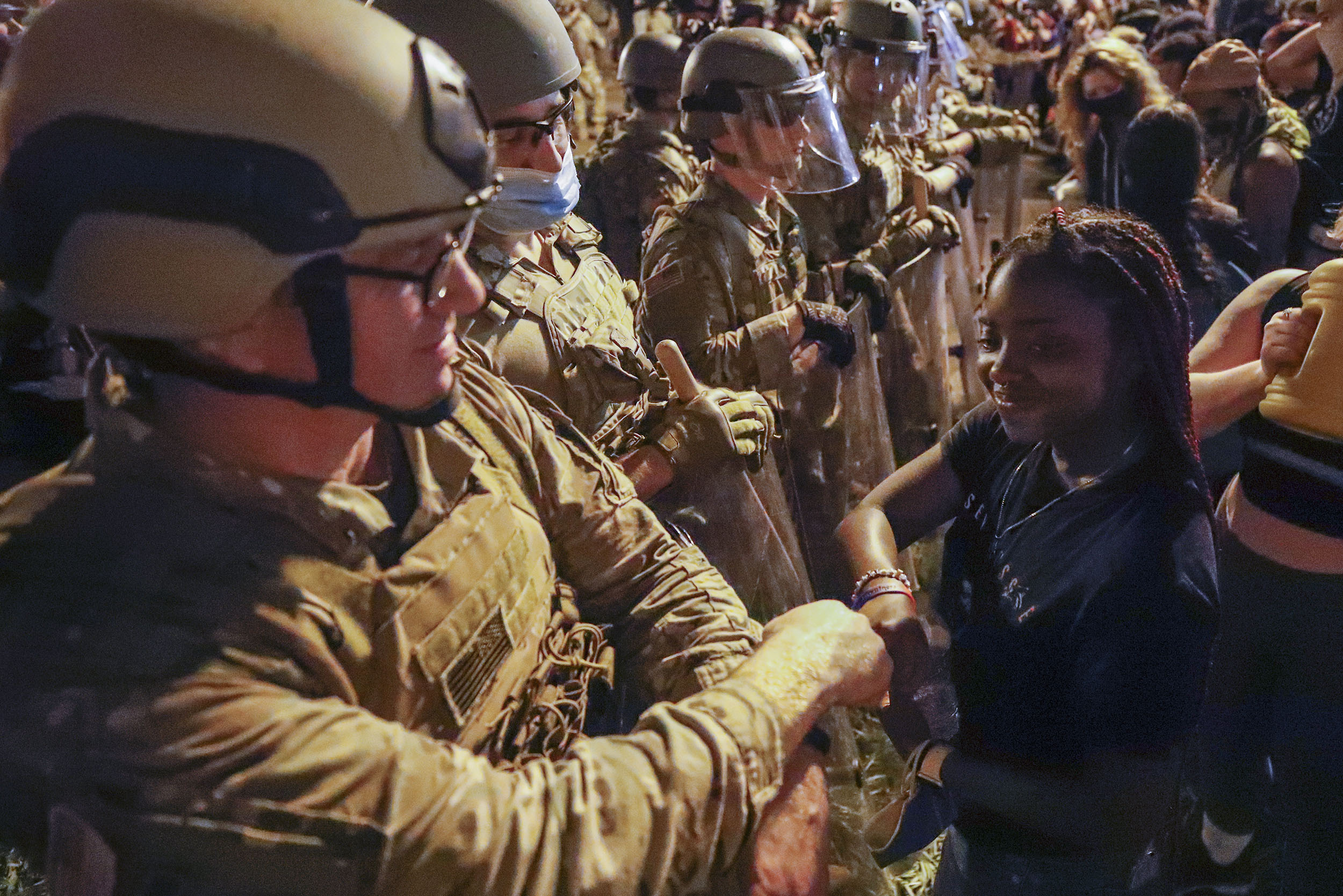 A Utah National Guard solider fist-bumps with a demonstrator as protests over the death of George Floyd continue in Washington DC, on Wednesday, June 3.