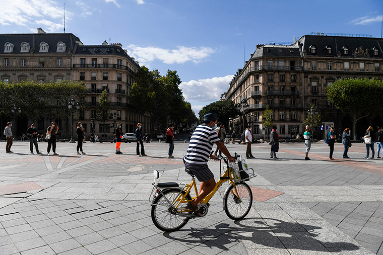 A man cycles as people wearing protective masks keep social distance as they wait in line for a PCR test for Covid-19 in front of the city hall of Paris on August 31.