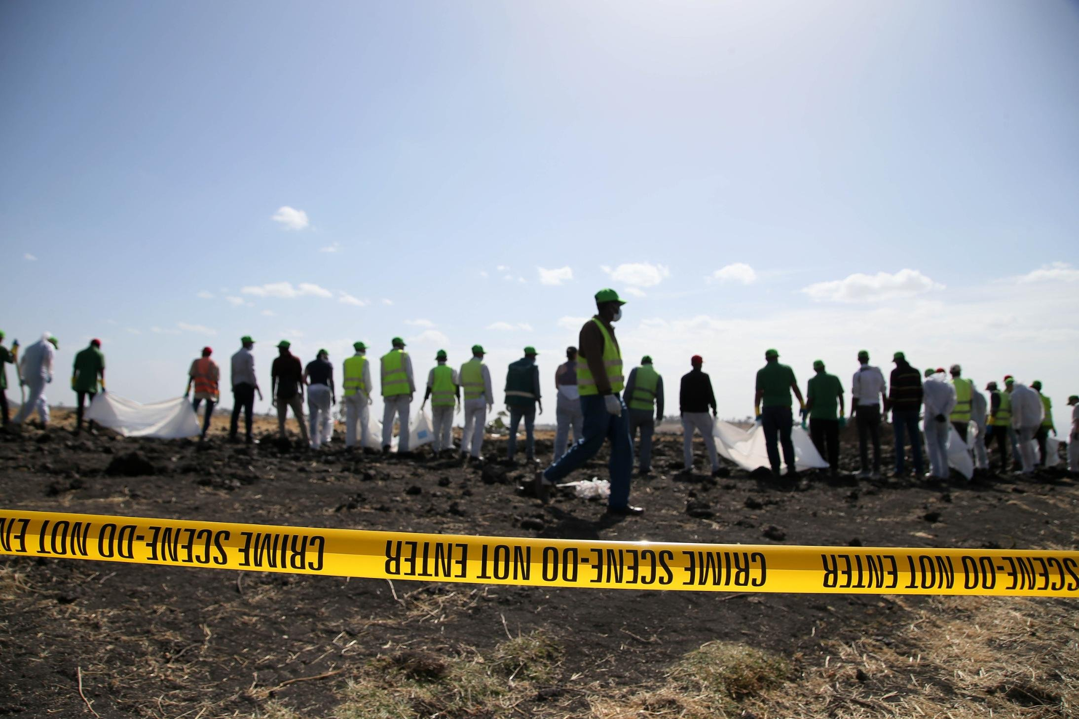 Forensics investigators and recovery teams work at the crash site near Bishoftu.