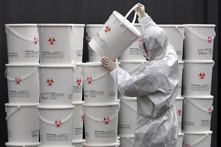 A worker in protective gear stacks plastic buckets containing medical waste from coronavirus patients at a medical center in Daegu, South Korea, Monday, February 24.