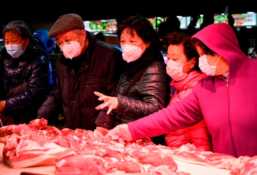People wearing protective face masks shop for meat at a market in Shanghai on February 14, 2020.