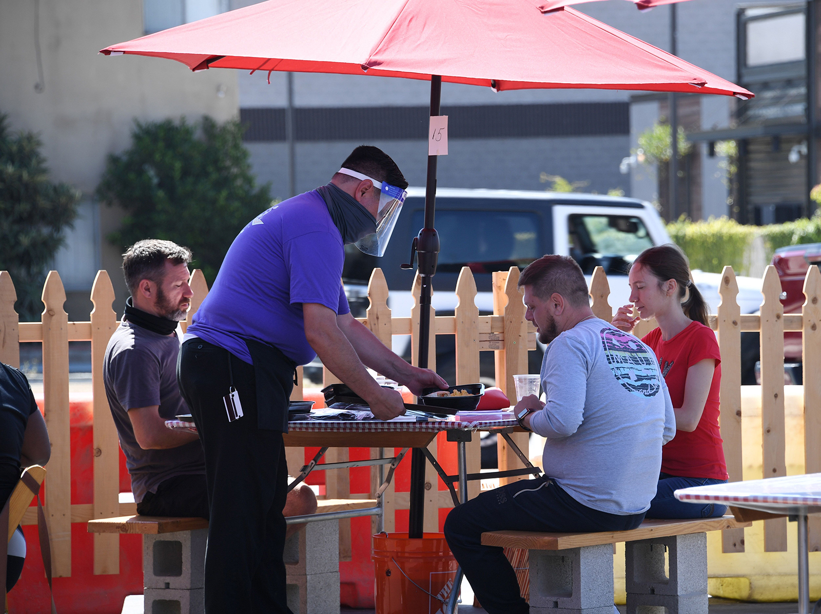 A waiter wearing protective gear serves food to customers on the patio at Pann's restaurant and coffee shop on July 4, in Los Angeles.