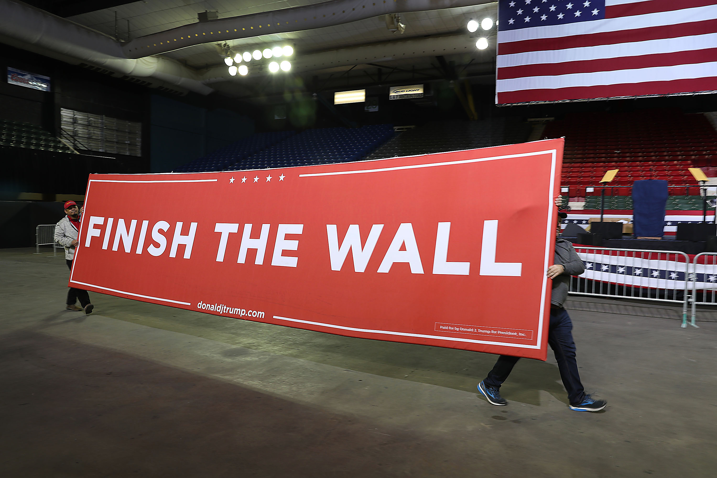 Workers carry a sign that reads 'Finish the Wall' as they prepare for the arrival of President Trump for a rally at the El Paso on Monday.