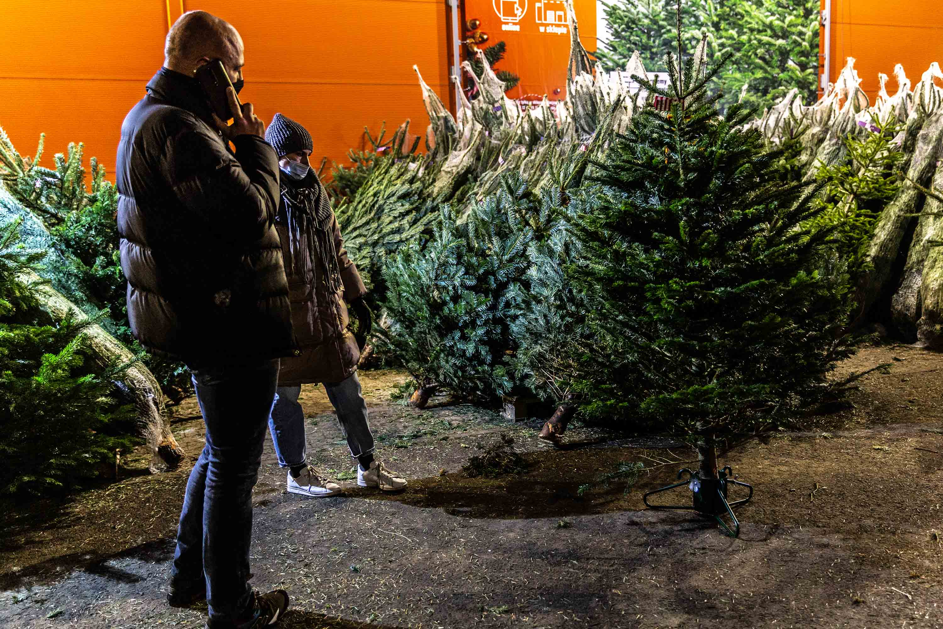 A couple is seen choosing a Christmas tree in Bronowice shopping mall in Krakow, Poland, as the city prepares for Christmas amid coronavirus restriction measures, on December 16.