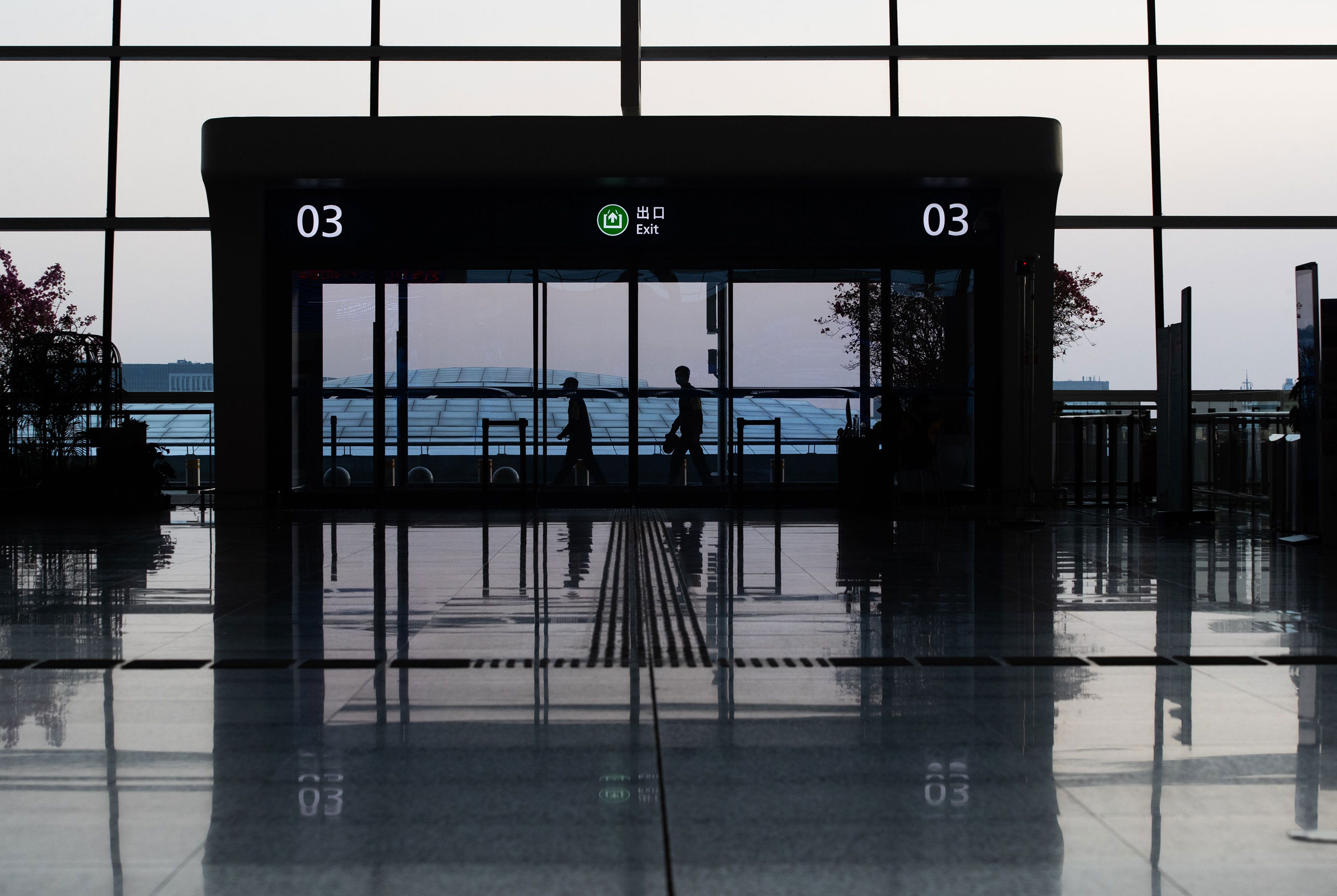 Workers walk through the nearly empty Wuhan Tianhe airport in Wuhan, China on March 17.