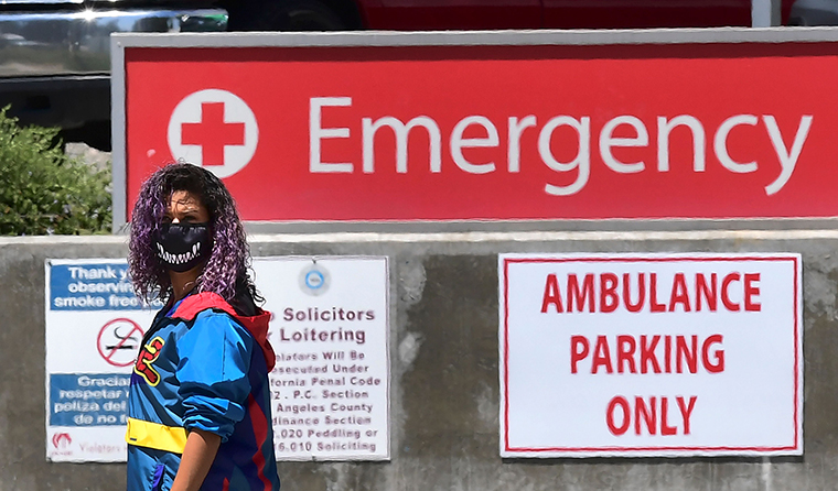 A woman wears a face-covering while walking past a sign leading to the Emergency section at the Los Angeles County+USC Medical Center in Los Angeles, on July 2.