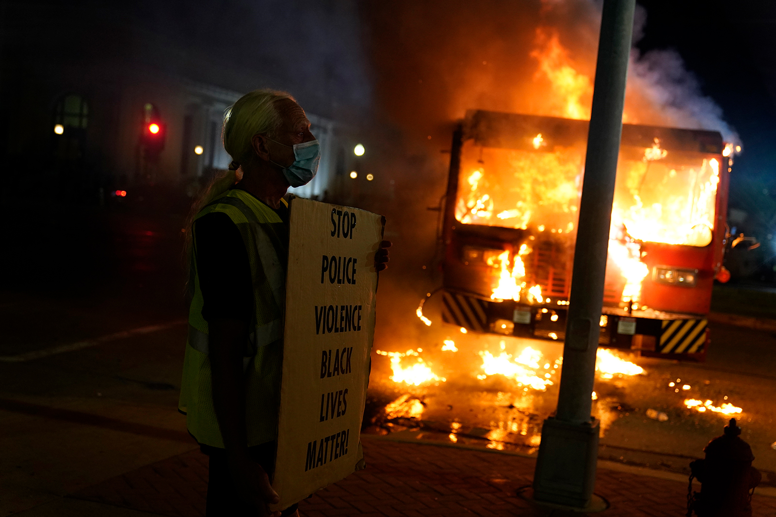 A protester stands near a burning garbage truck outside the Kenosha County Courthouse, in Kenosha, Wisconsin late, on August 24.