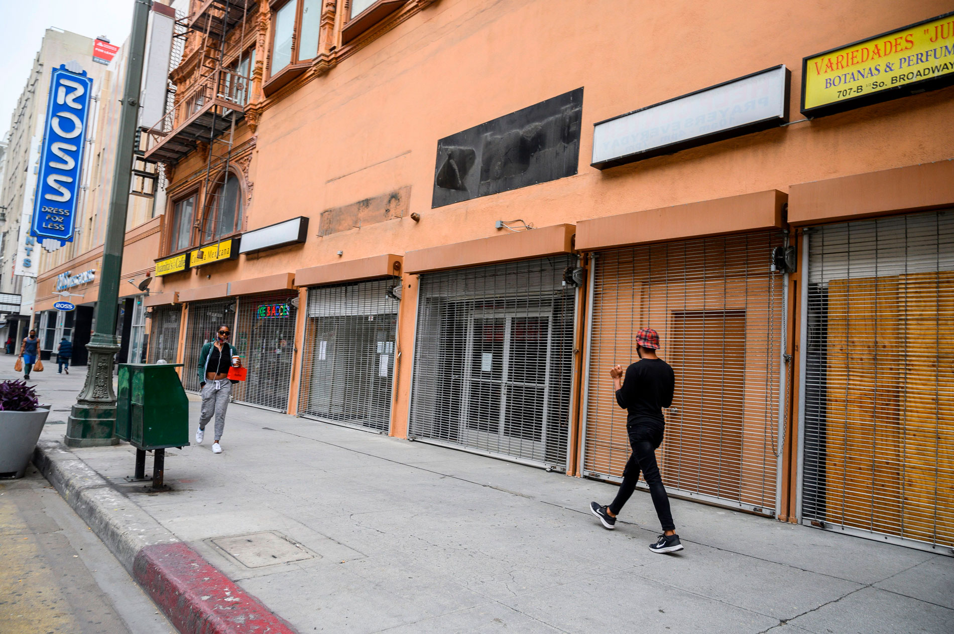 People walk past closed shops in downtown Los Angeles, on April 30.