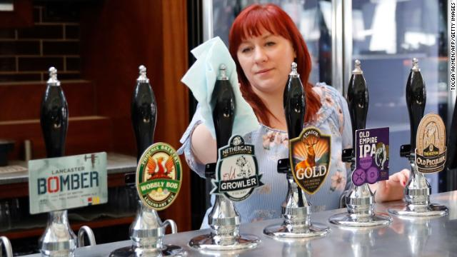 A member of staff at a pub in north London cleans the bar on June 24 in preparation for pubs to reopen.
