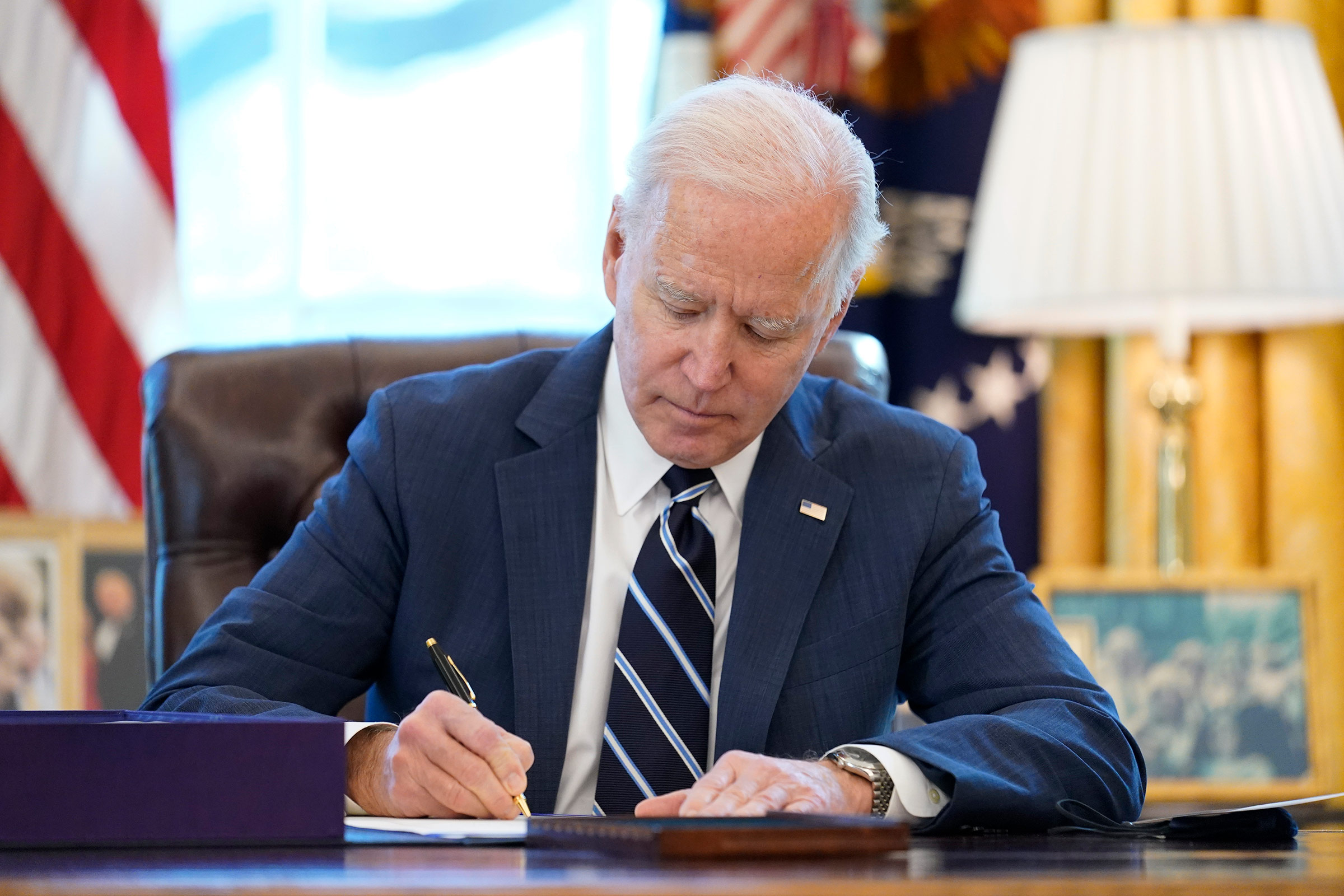 President Joe Biden signs the American Rescue Plan in the Oval Office of the White House on March 11, in Washington, DC.