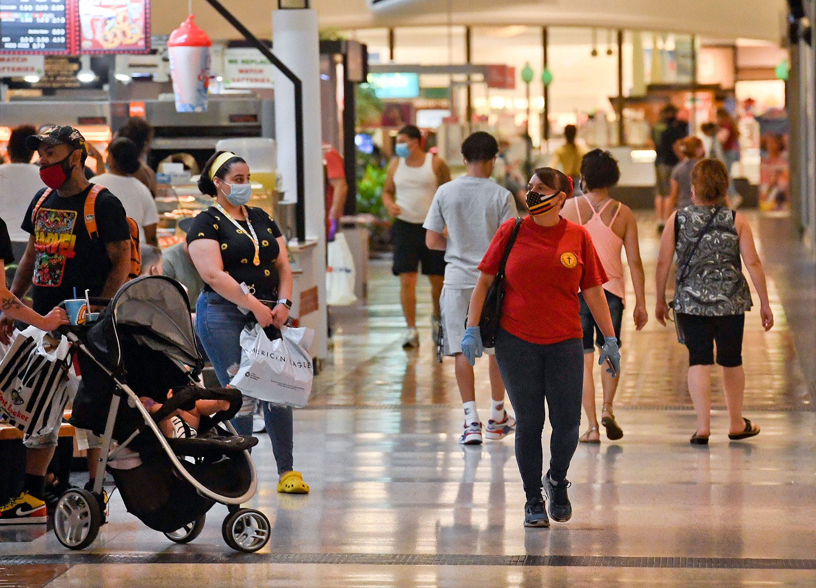 People wearing masks walk through the Berkshire Mall in Wyomissing, Pennsylvania, on June 26. Pennsylvania Gov. Tom Wolf announced a new order that requires masks to be worn whenever anyone leaves home.