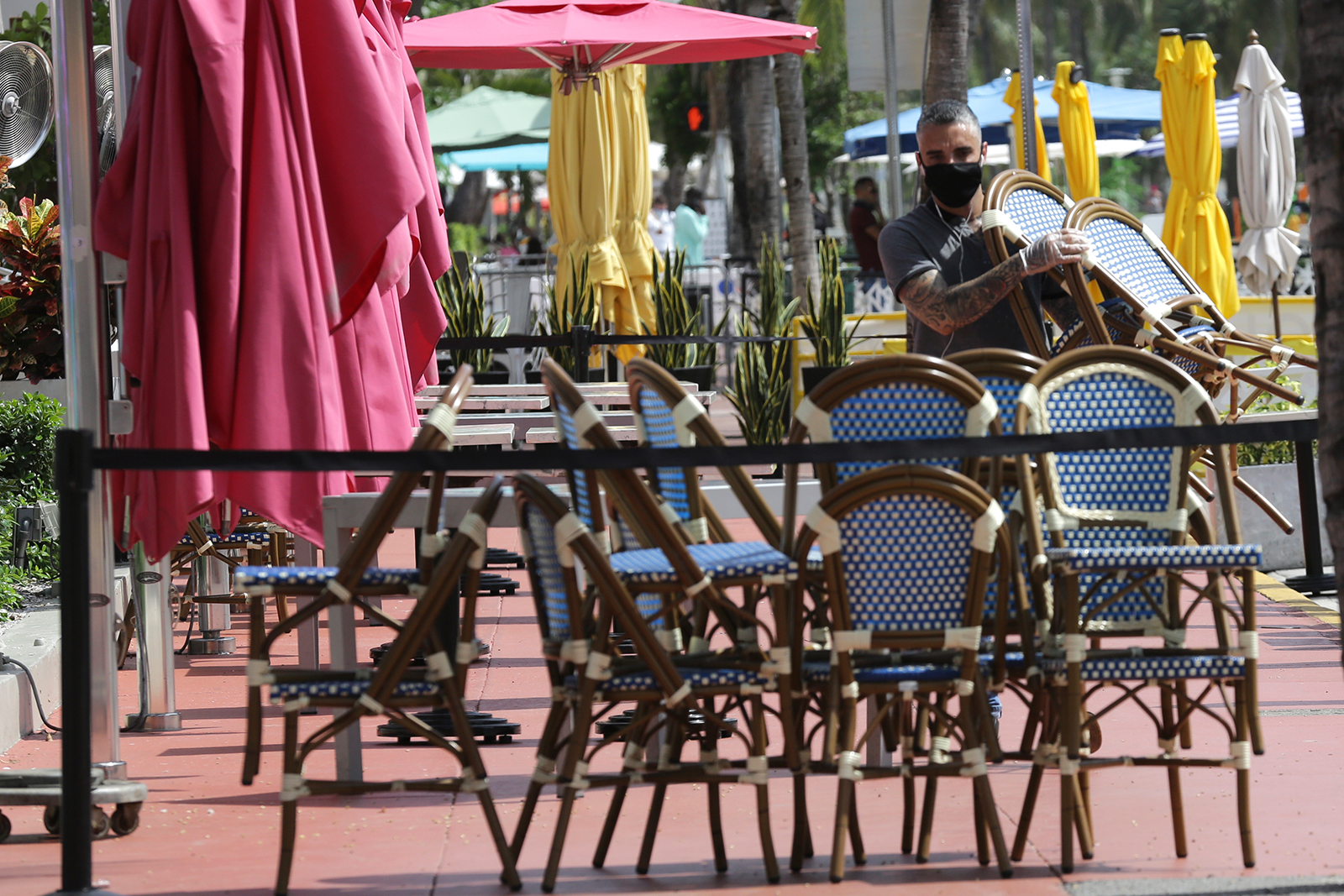 An employee at the Clevelander bar and restaurant stacks chairs as they have shut down due to public health concerns caused by Covid-19 in Miami Beach, Florida on July 13.