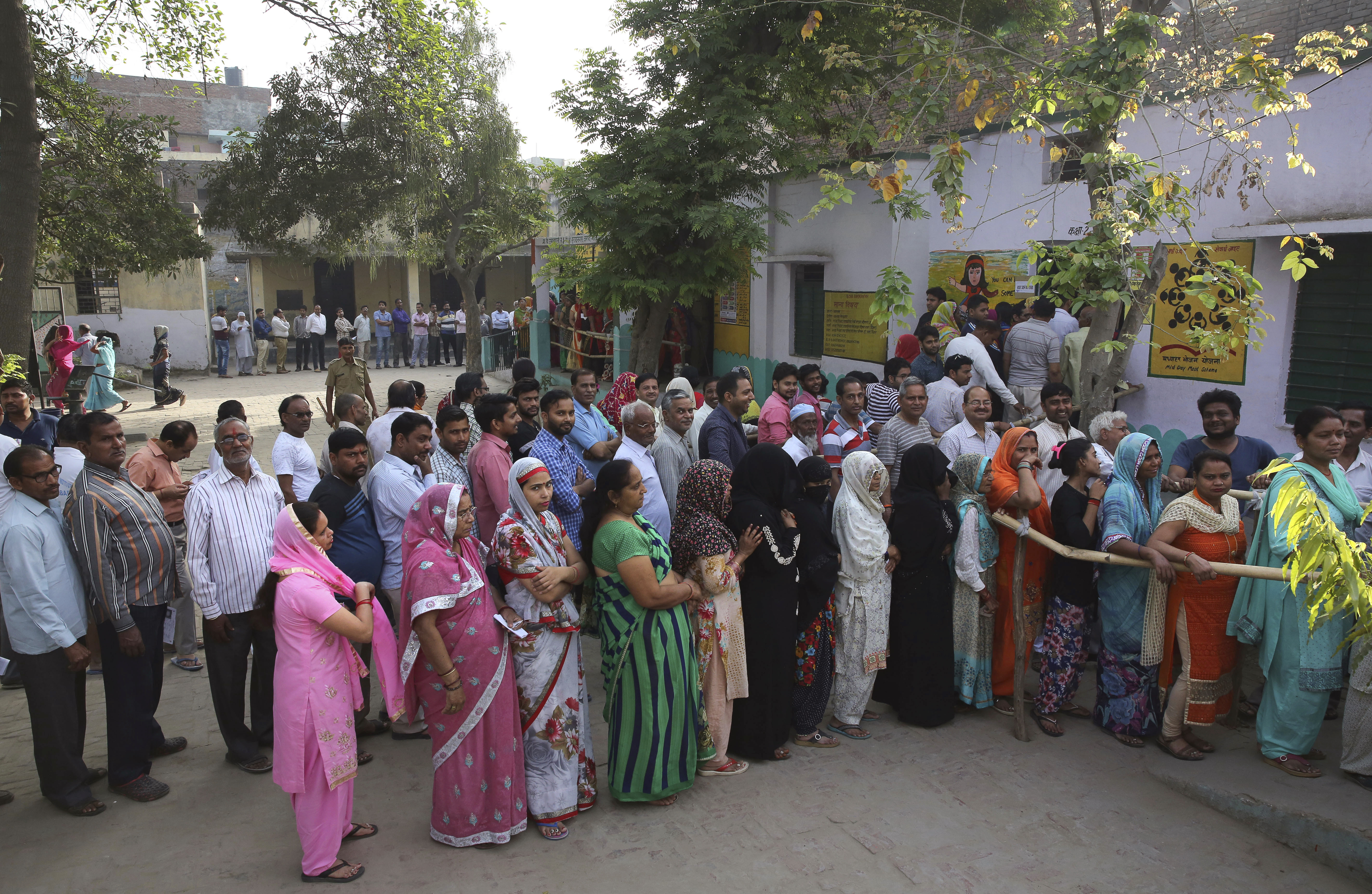 People queue to cast their votes at a polling booth for the first phase of general elections, near Ghaziabad in Uttar Pradesh on April 11, 2019.