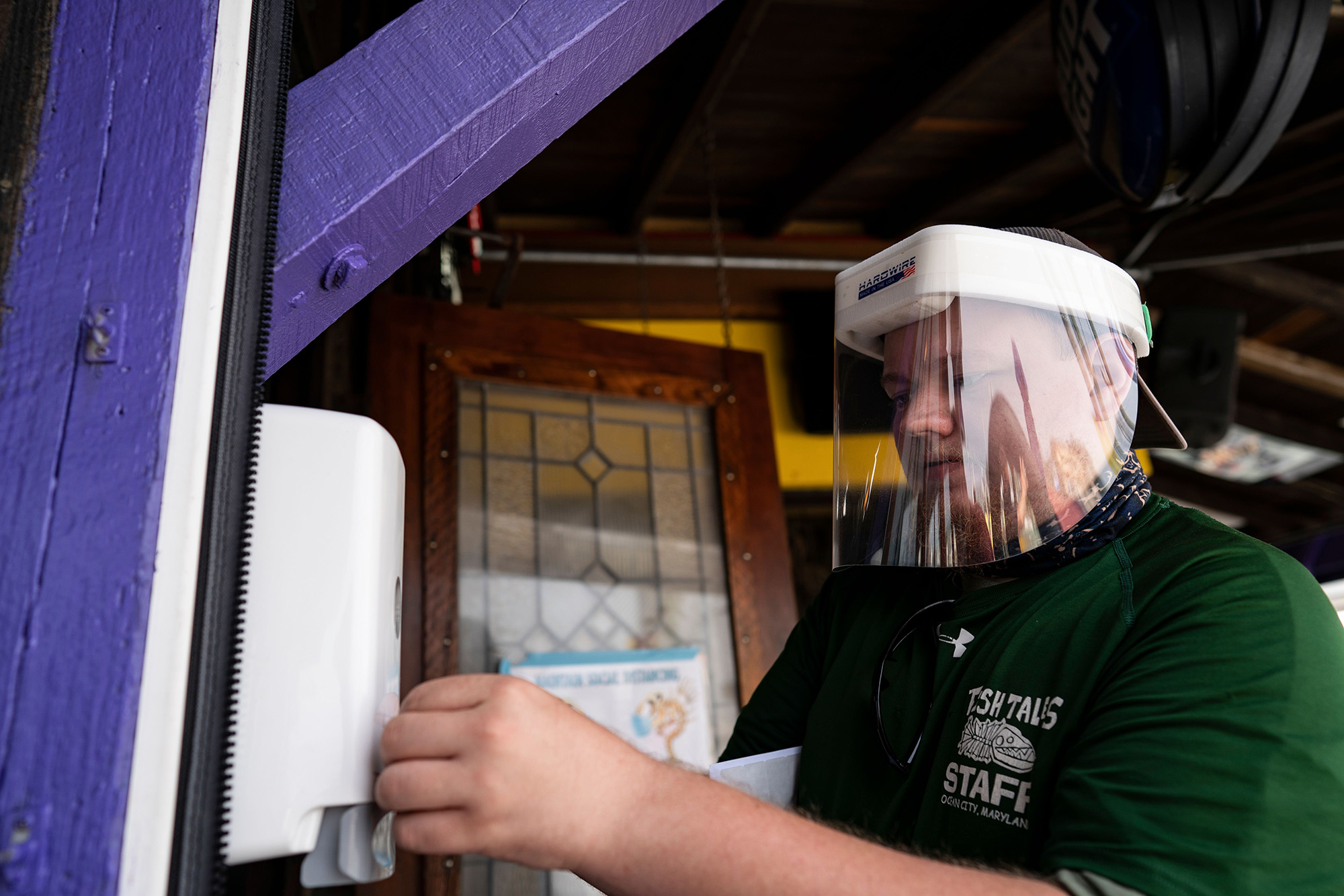 A restaurant employee with a hand sanitizer dispenser in Ocean City, Maryland, on May 29.