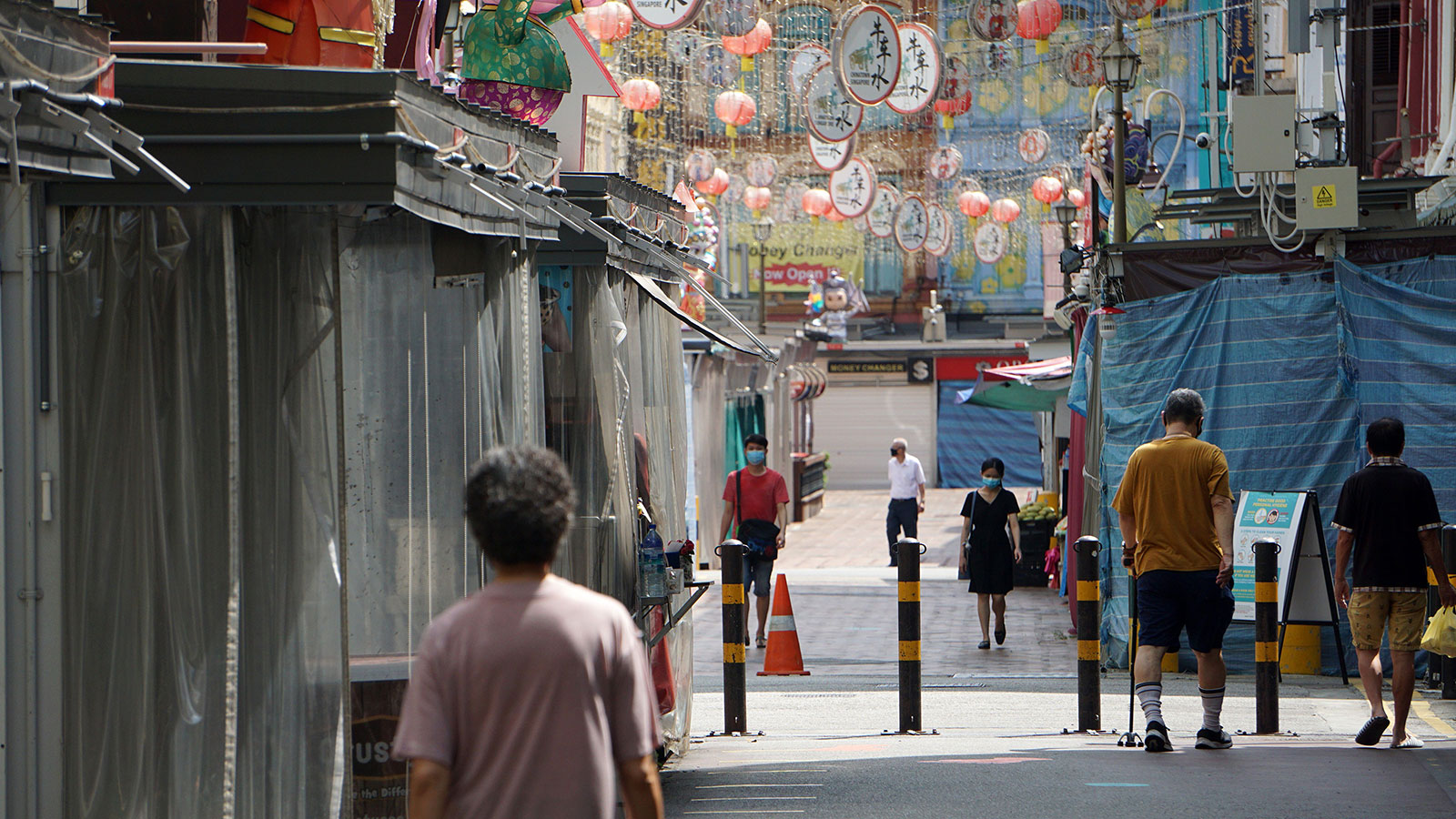 People walk past closed shops in the Chinatown district of Singapore on April 13.