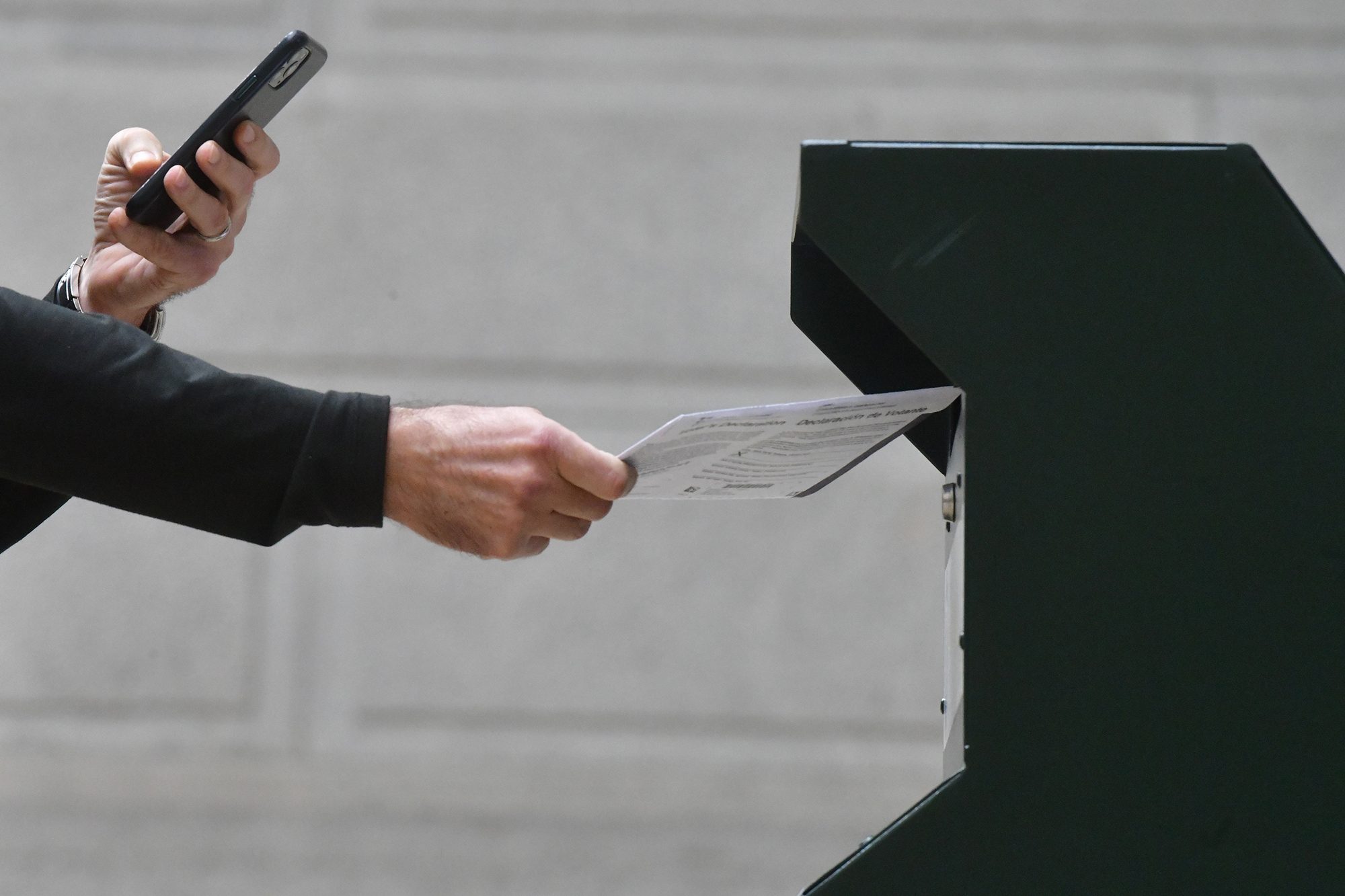 A man photographs himself depositing his ballot in an official ballot drop box while a long line of voters queue outside of Philadelphia City Hall at the satellite polling station on October 27, in Philadelphia, Pennsylvania.