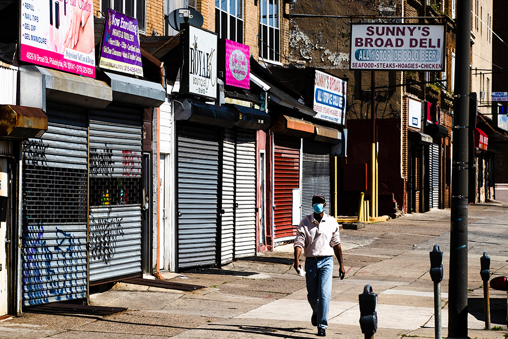 A person wearing a protective face mask as a precaution against the coronavirus walks past stuttered businesses in Philadelphia, on Thursday, May 7.
