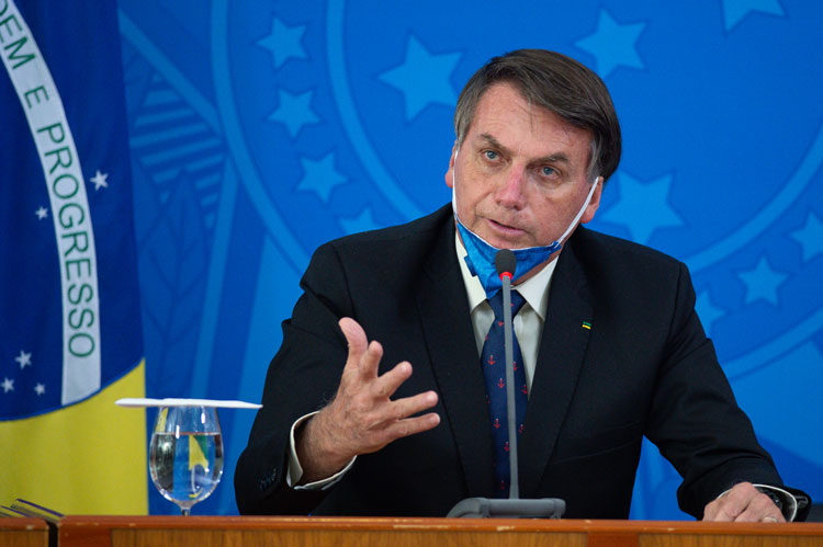 Brazilian President Jair Bolsonaro takes off his protective mask to speak to journalists during a news conference about the outbreak of the coronavirus at the Planalto Palace on March 20 in Brasilia, Brazil.