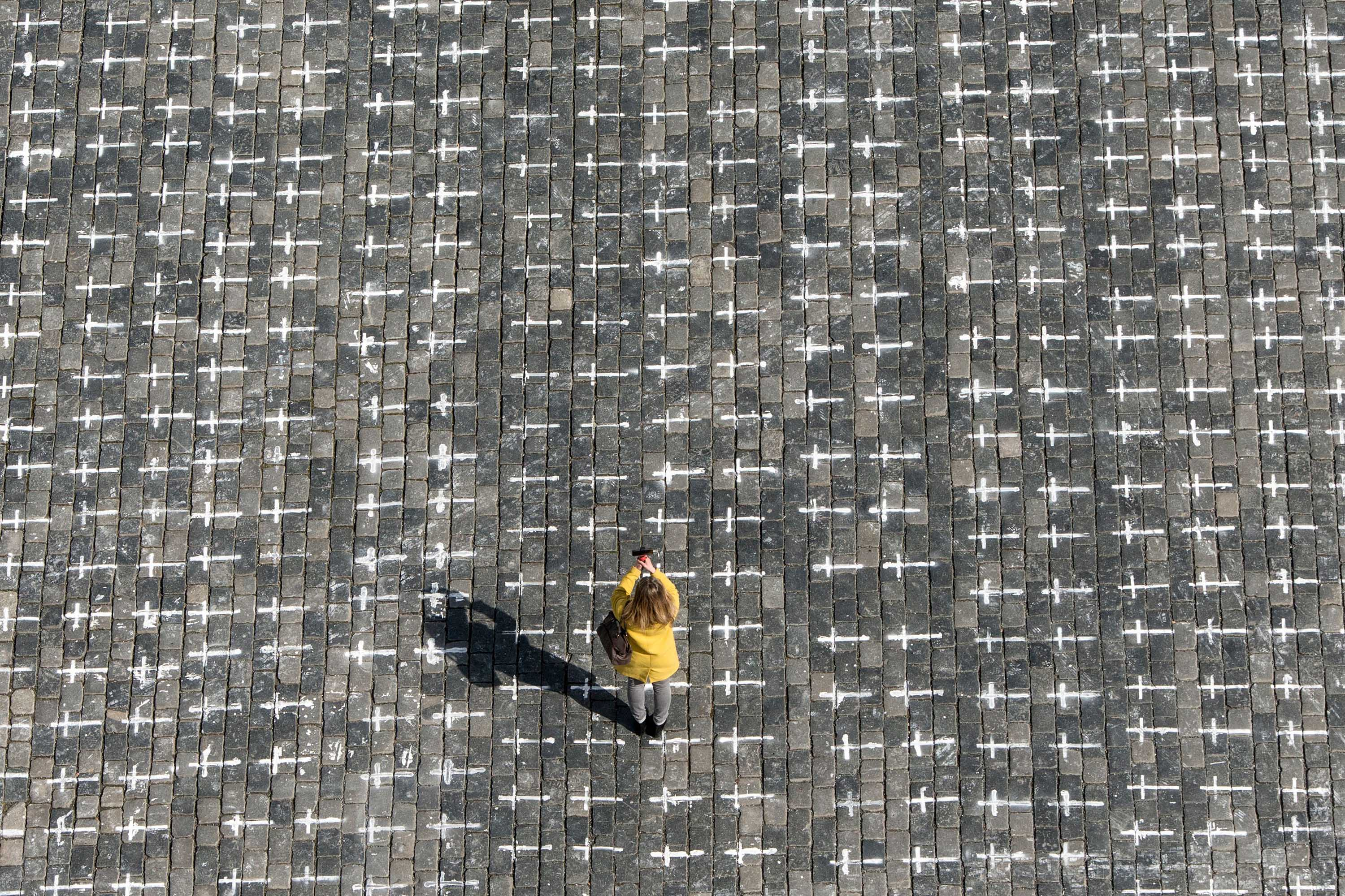 A person takes a photo at the Old Town Square in Prague, Czech Republic, on March 22, where thousands of crosses have been drawn on the pavement to commemorate the first anniversary since the death of the first Czech coronavirus patient.