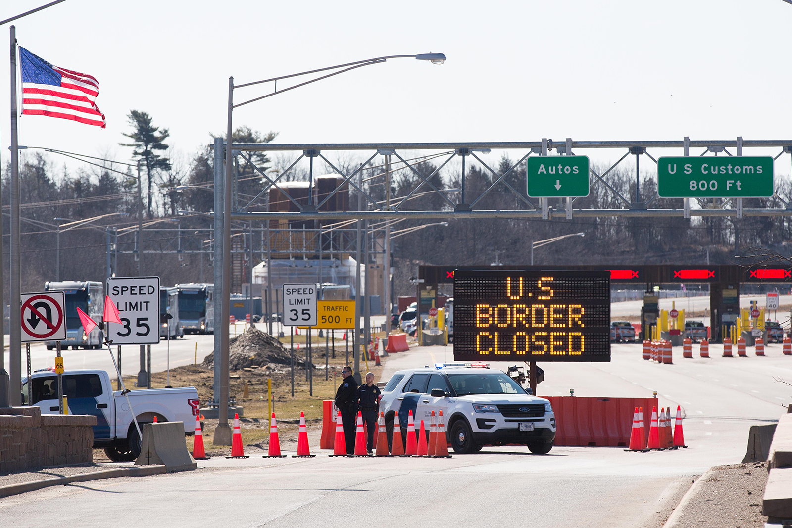 US Customs officers stand beside a sign saying that the US border is closed at the US-Canada border in Lansdowne, Ontario, on March 22.