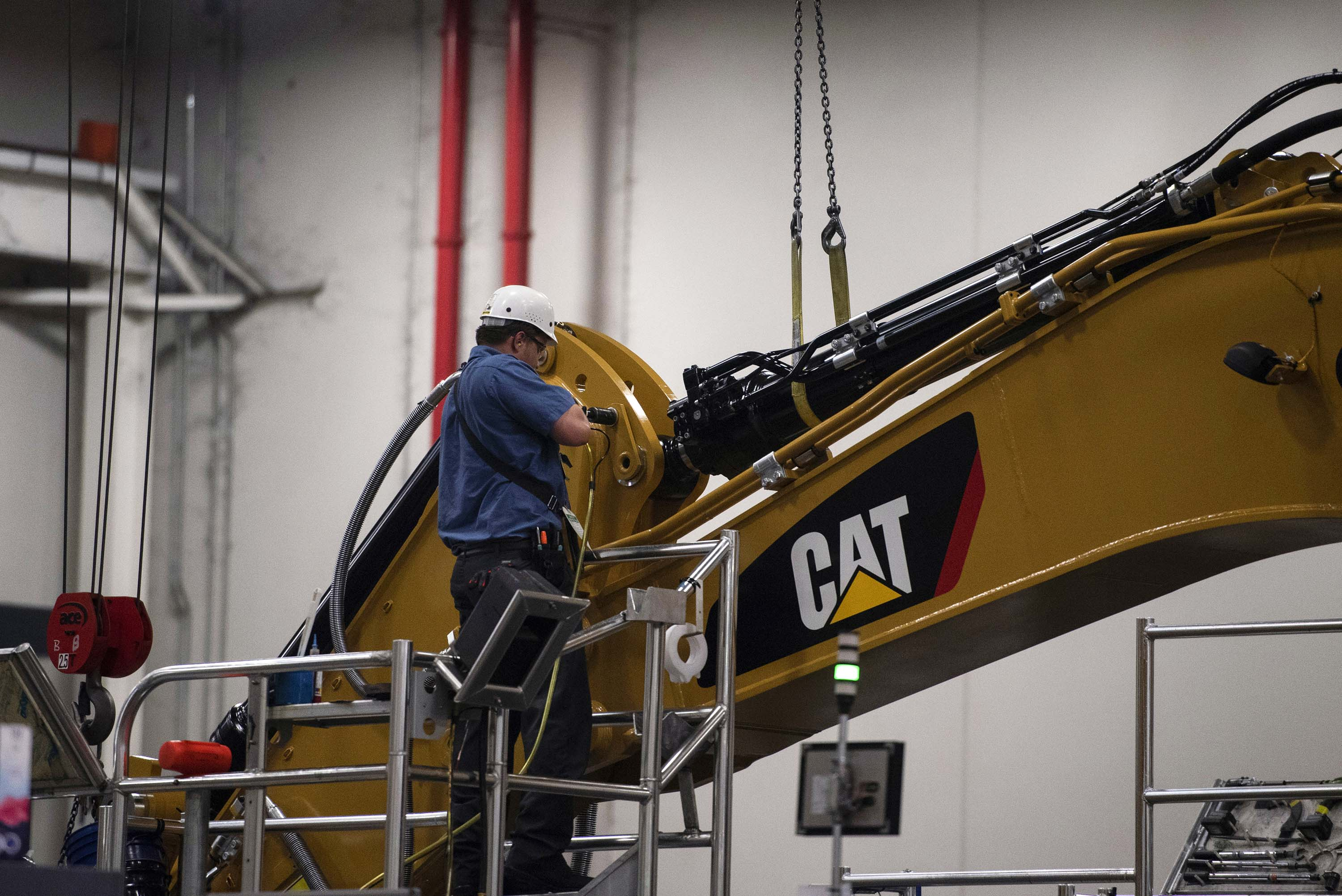 An employee assembles an excavator stick at the Caterpillar Inc. manufacturing facility in Victoria, Texas, in August 2018.