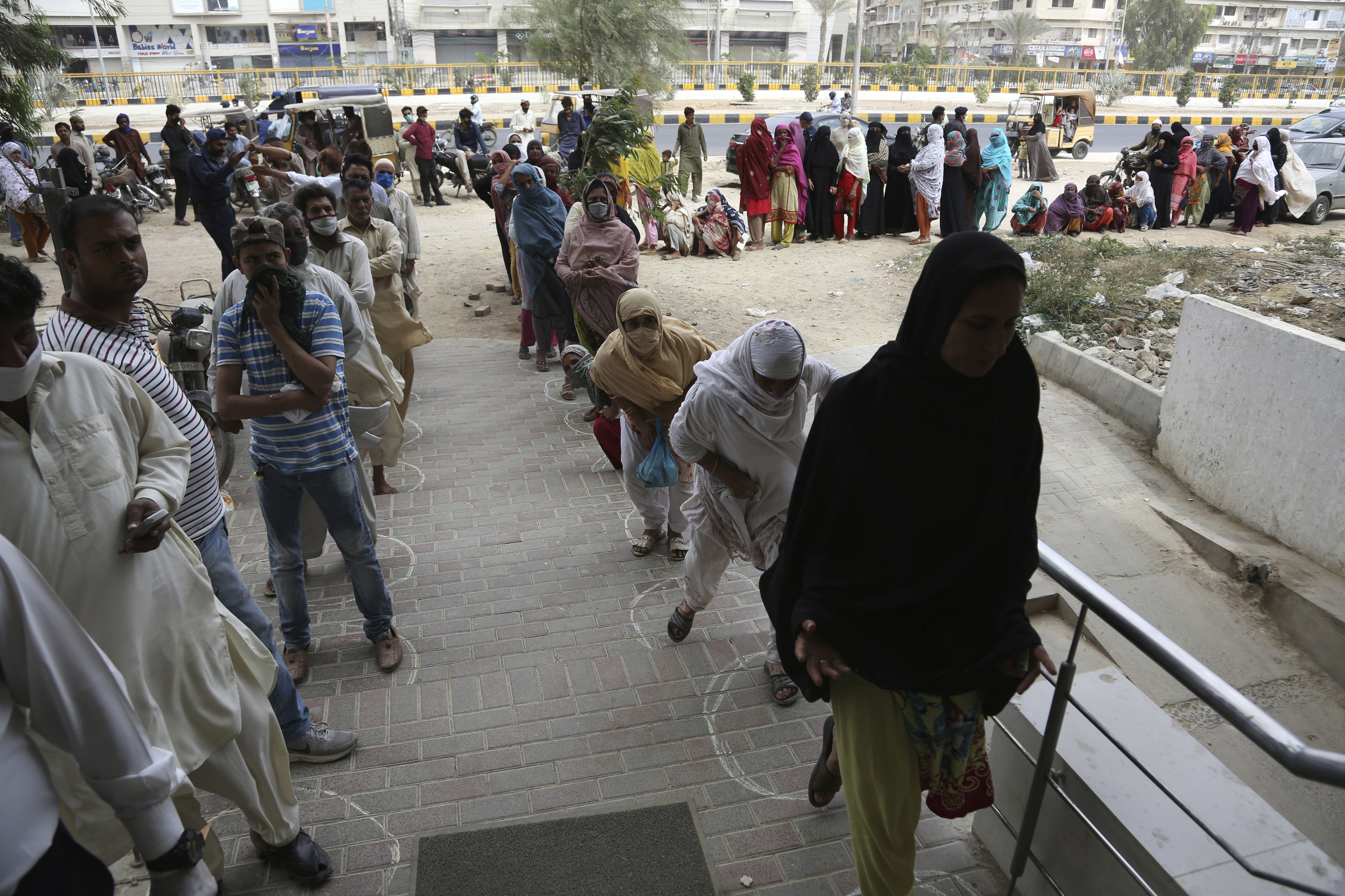 People wait to receive cash under the government's Ehsaas Emergency Cash program for families in need in Karachi, Pakistan, on April 14.